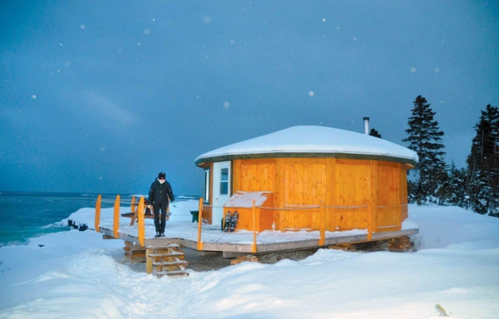 Une yourte située à 90 minutes en raquettes de la base de plein air Les Goélands, à Port-Cartier. En bas, à gauche, la baie de la Goélette et, à droite, des traîneaux à chiens à la base de plein air.<br />