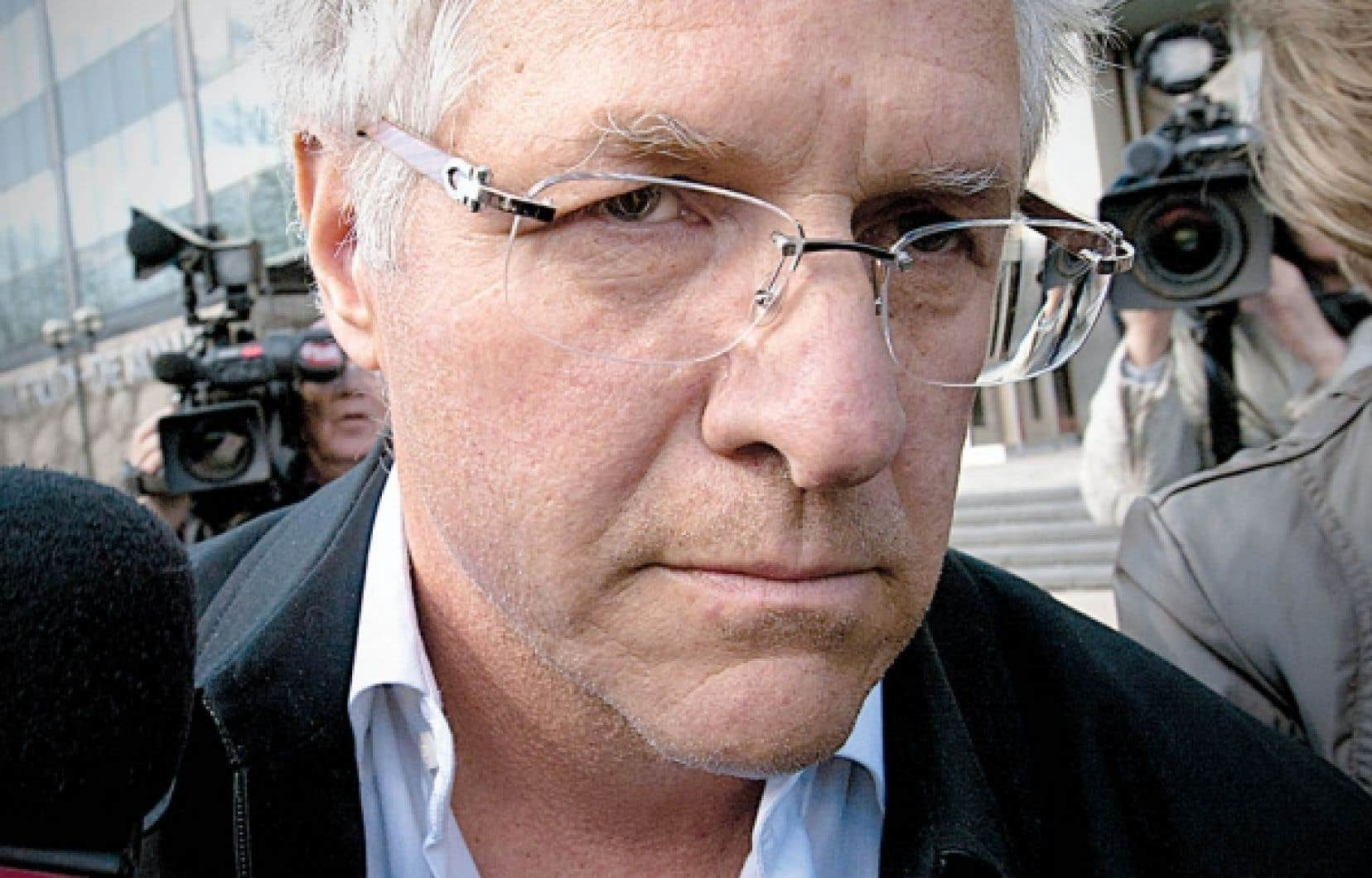 L'entrepreneur Tony Accurso entouré de journalistes à sa sortie du quartier général de la Sûreté du Québec, rue Parthenais, à Montréal, hier. Des accusations de fraude, complot, abus de confiance et trafic d'influence ont été portées contre lui.<br />