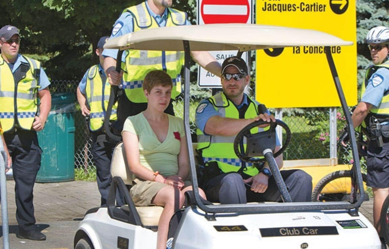 <div> Une jeune femme portant le carré rouge est escortée par les policiers.</div>