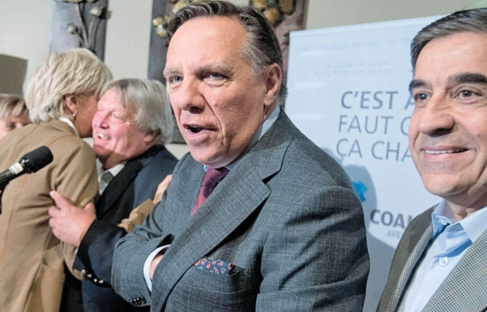 Le chef de la Coalition avenir Québec, François Legault, et son candidat vedette Gaétan Barrette (à gauche), accompagnés d'un pharmacien, ont maintenu hier qu'ils ont la solution pour que chaque Québécois ait son médecin de famille.