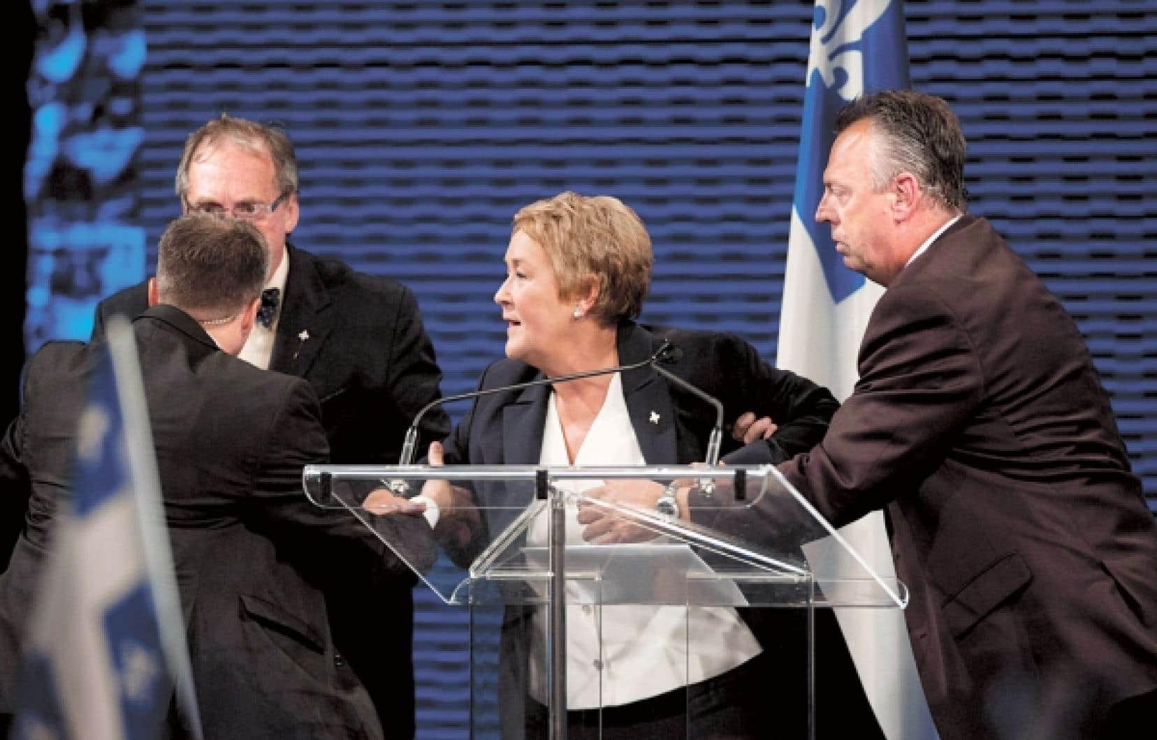 Pauline Marois, entraînée hors de la scène lors de son discours de victoire au Métropolis, le 4 septembre.