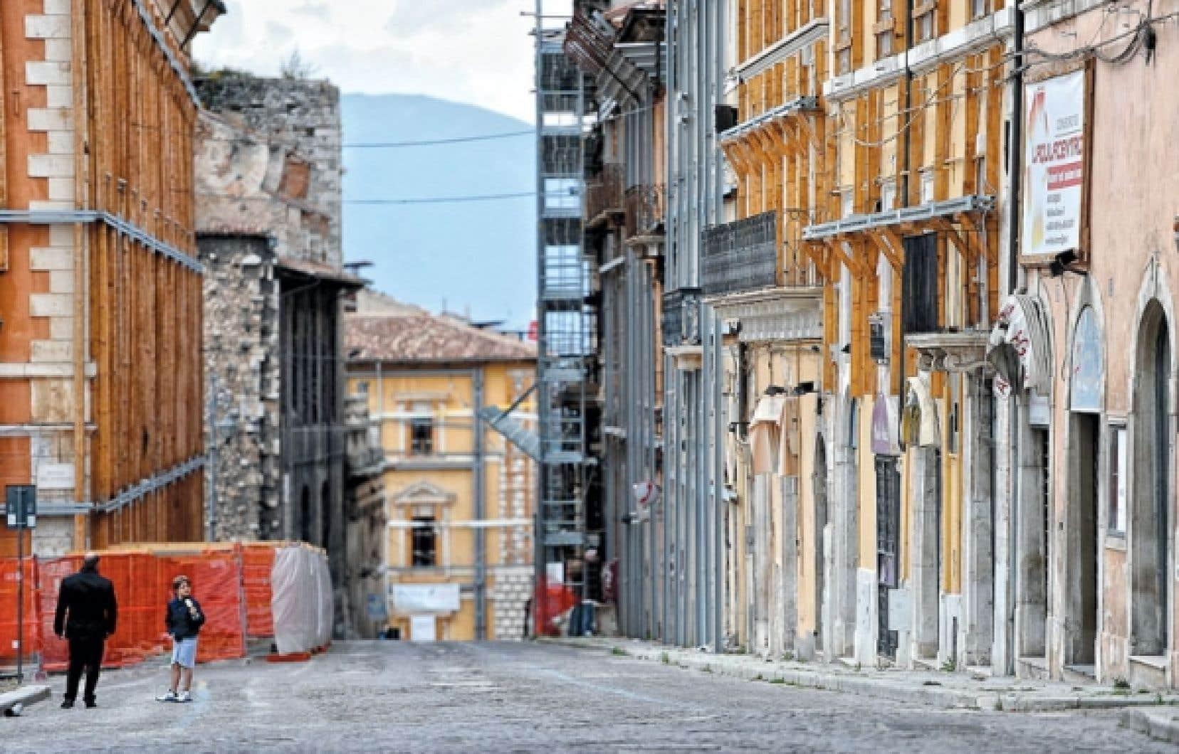 Des résidants d'Aquila près de la zone rouge encore fermée au public, dans le quartier historique de la ville