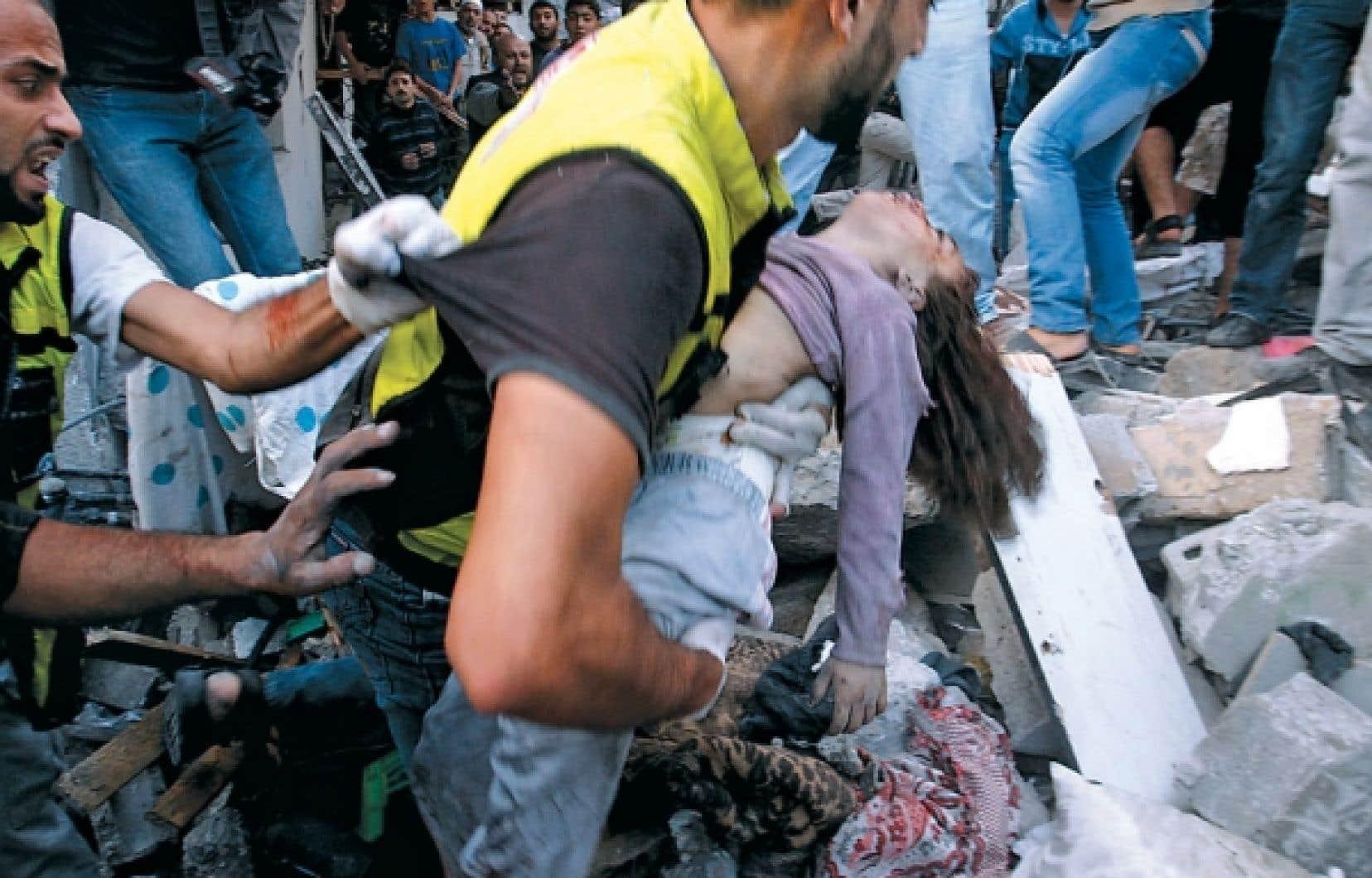 Un secouriste transporte une enfant retirée des décombres d'une maison de Gaza bombardée par l'armée israélienne. L'opération militaire de dimanche a causé la mort d'au moins 29 personnes, dont la moitié étaient des femmes et des enfants, selon les autorités médicales de Gaza.