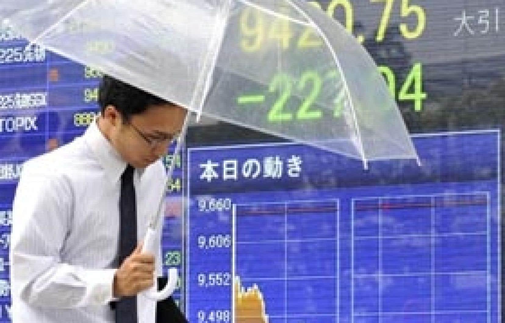 Un homme d'affaires japonais devant un tableau électronique indiquant les cotes de la Bourse. À l'image de la Bourse de Toronto, le Tokyo Stock Exchange a chuté, hier.