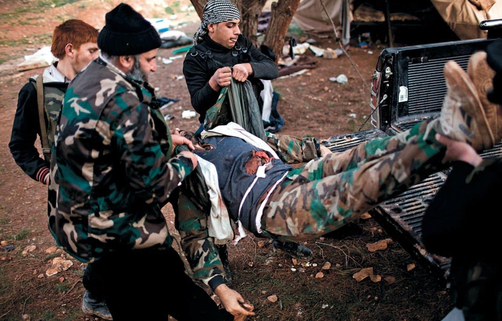 <div> Des combattants rebelles déplaçant le corps d'un soldat des forces gouvernementales après de violents affrontements dans la ville de Sheer Tal, en Syrie, dimanche.</div>