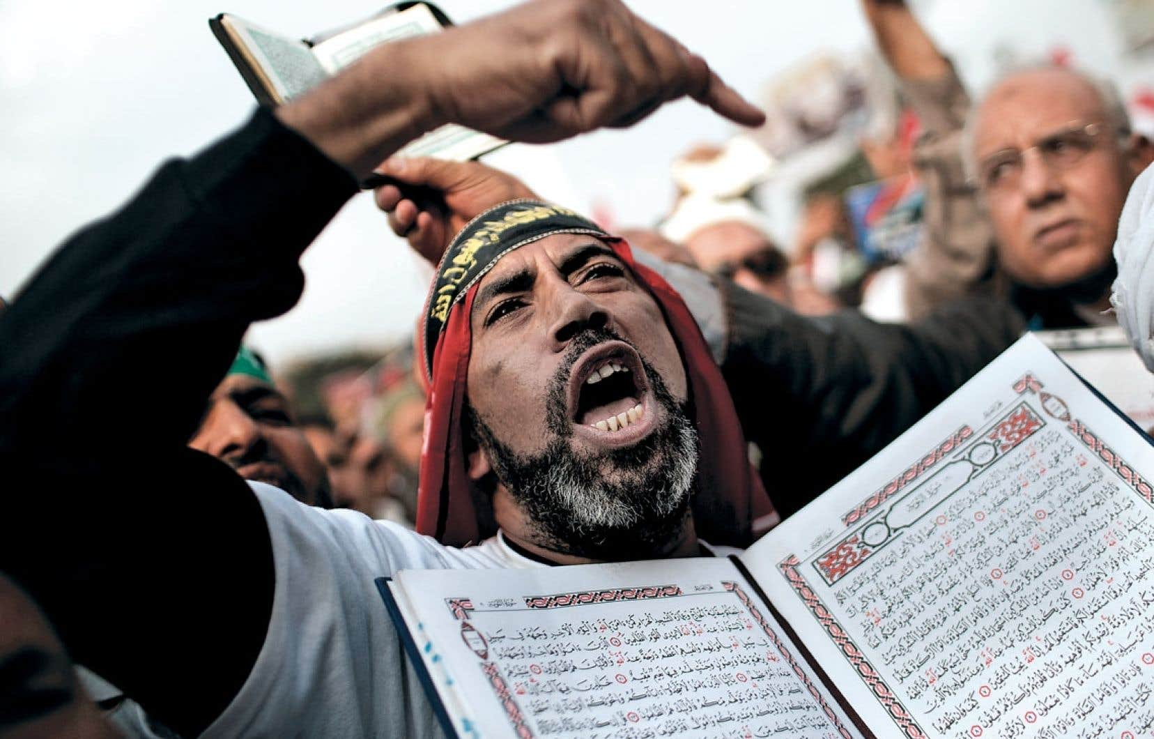 <div> Un partisan des Frères musulmans avec un exemplaire du Coran lors d'une manifestation au Caire. Selon les islamistes, le « oui » l'a emporté alors que plusieurs dénoncent des irrégularités lors du vote.</div>