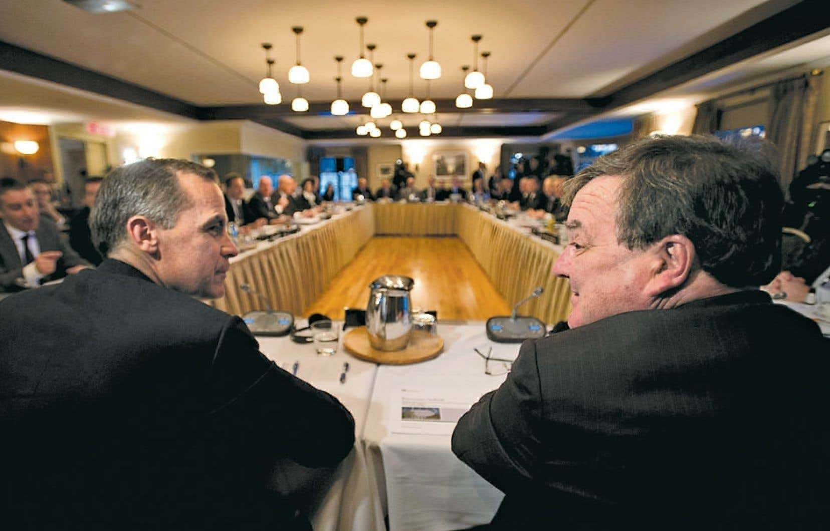 Le ministre canadien des Finances, Jim Flaherty (à droite), discute avec le gouverneur de la Banque du Canada, Mark Carney, avant que ne débute la réunion des ministres des Finances.