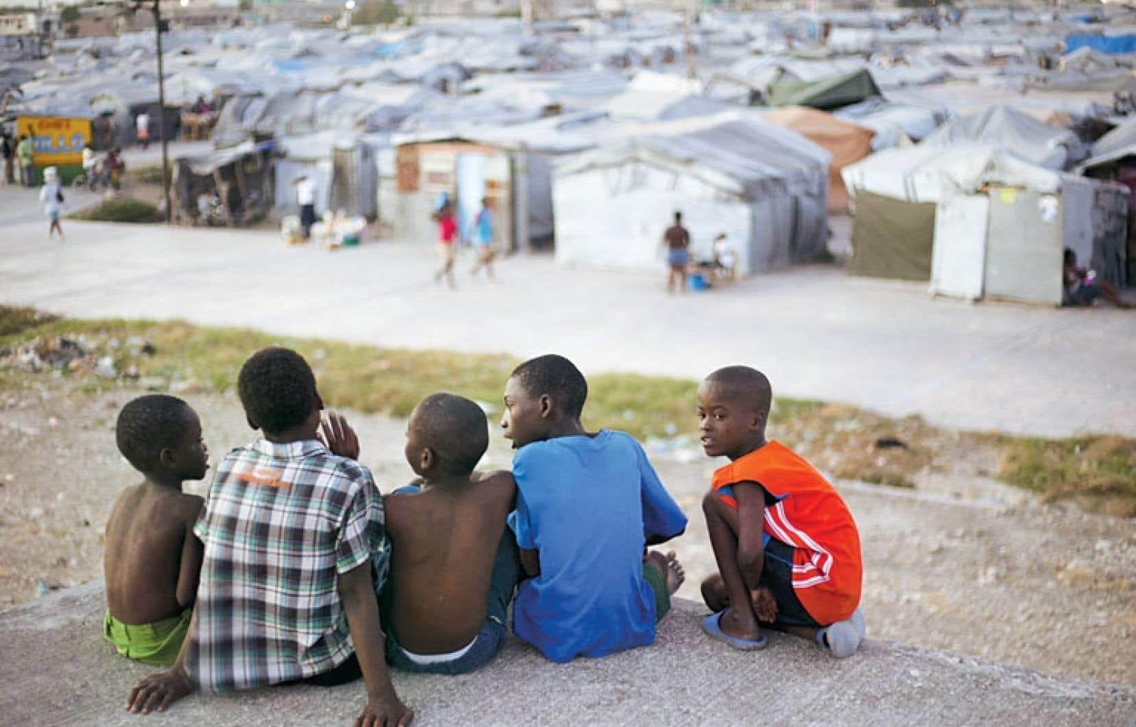Assis sur le toit d'une maison endommagée par le séisme de 2010, des jeunes garçons contemplent le camp Jean-Marie-Vincent, à Port-au-Prince, où ils résident toujours, trois ans après le drame.