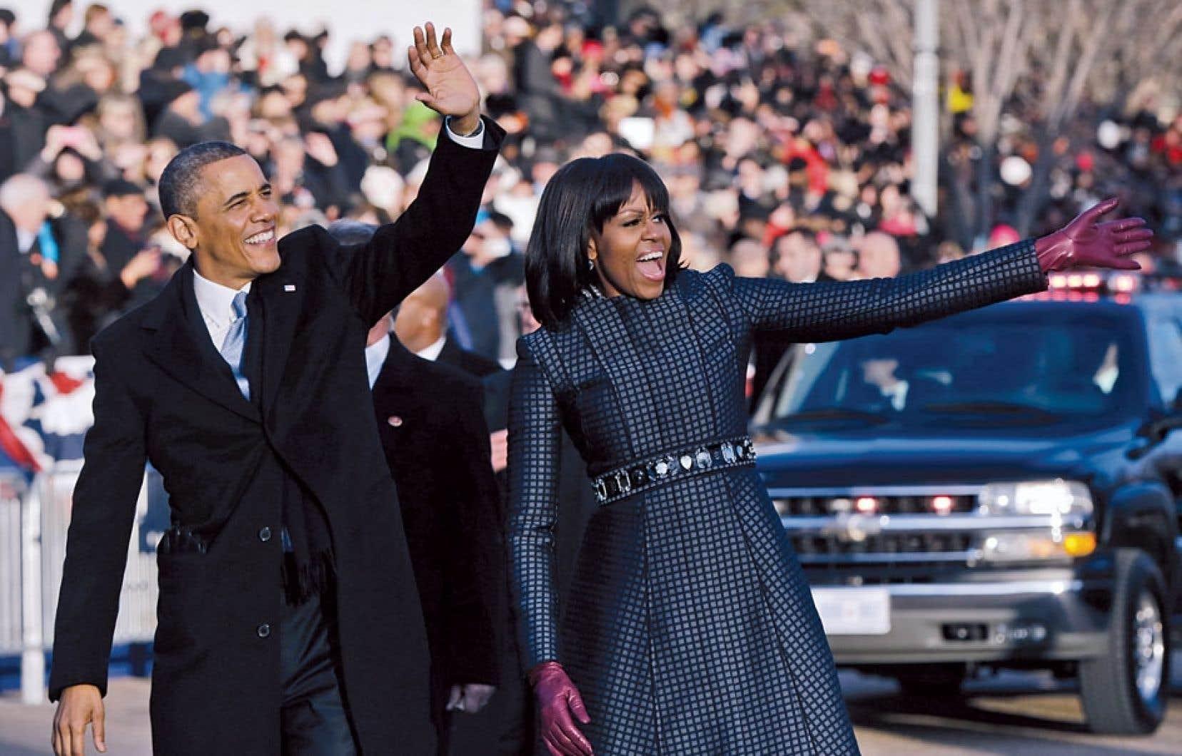 Barack Obama et sa femme, Michelle Obama, saluant la foule lors du défilé qui les a menés du Capitole jusqu'à la Maison-Blanche après la cérémonie d'investiture qui s'est déroulée lundi à Washington.