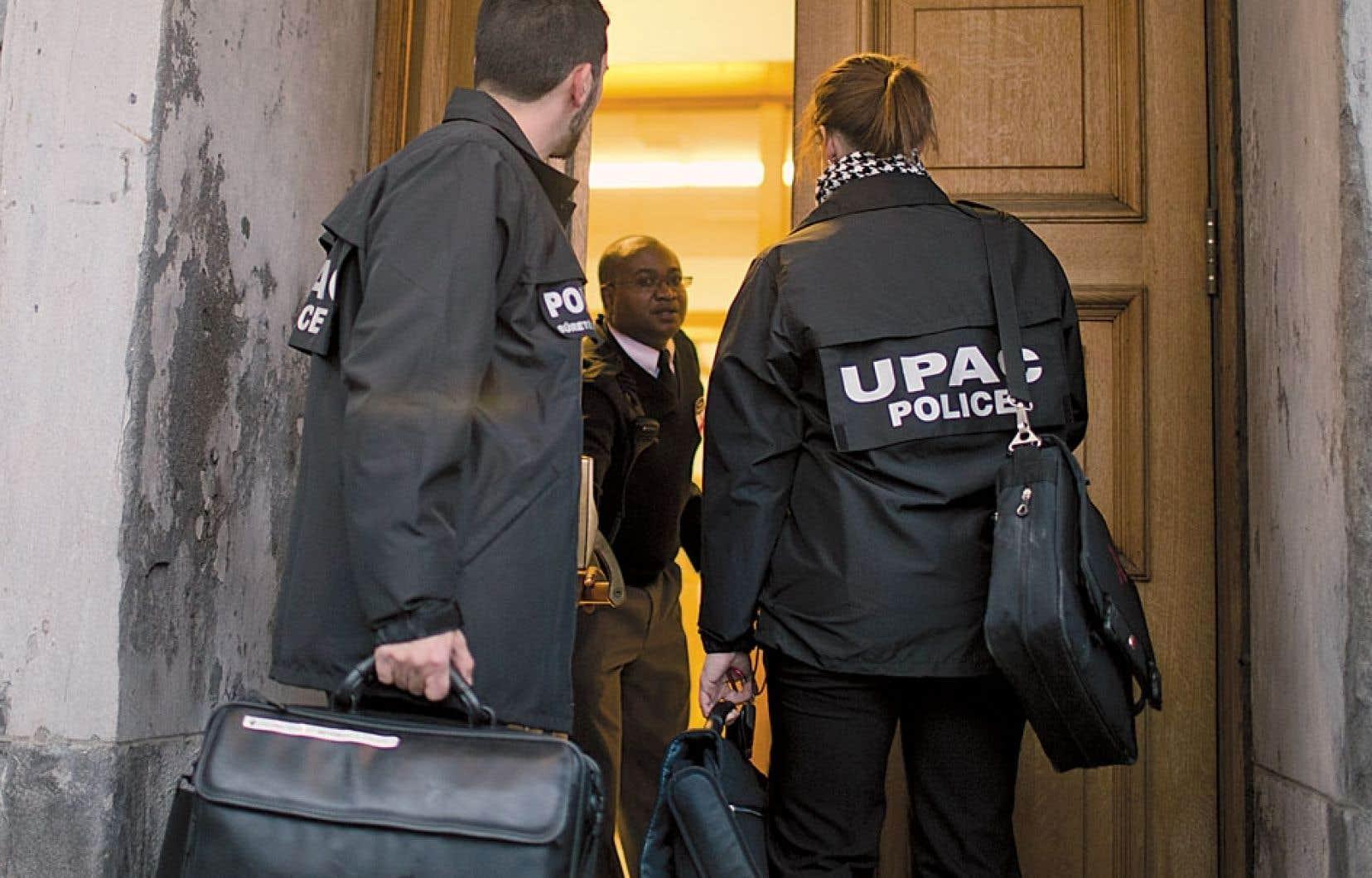 Des policiers de l'UPAC pénètrent à l'hôtel de ville de Montréal dans le cadre d'une perquisition-surprise menée en fin d'après-midi mardi.