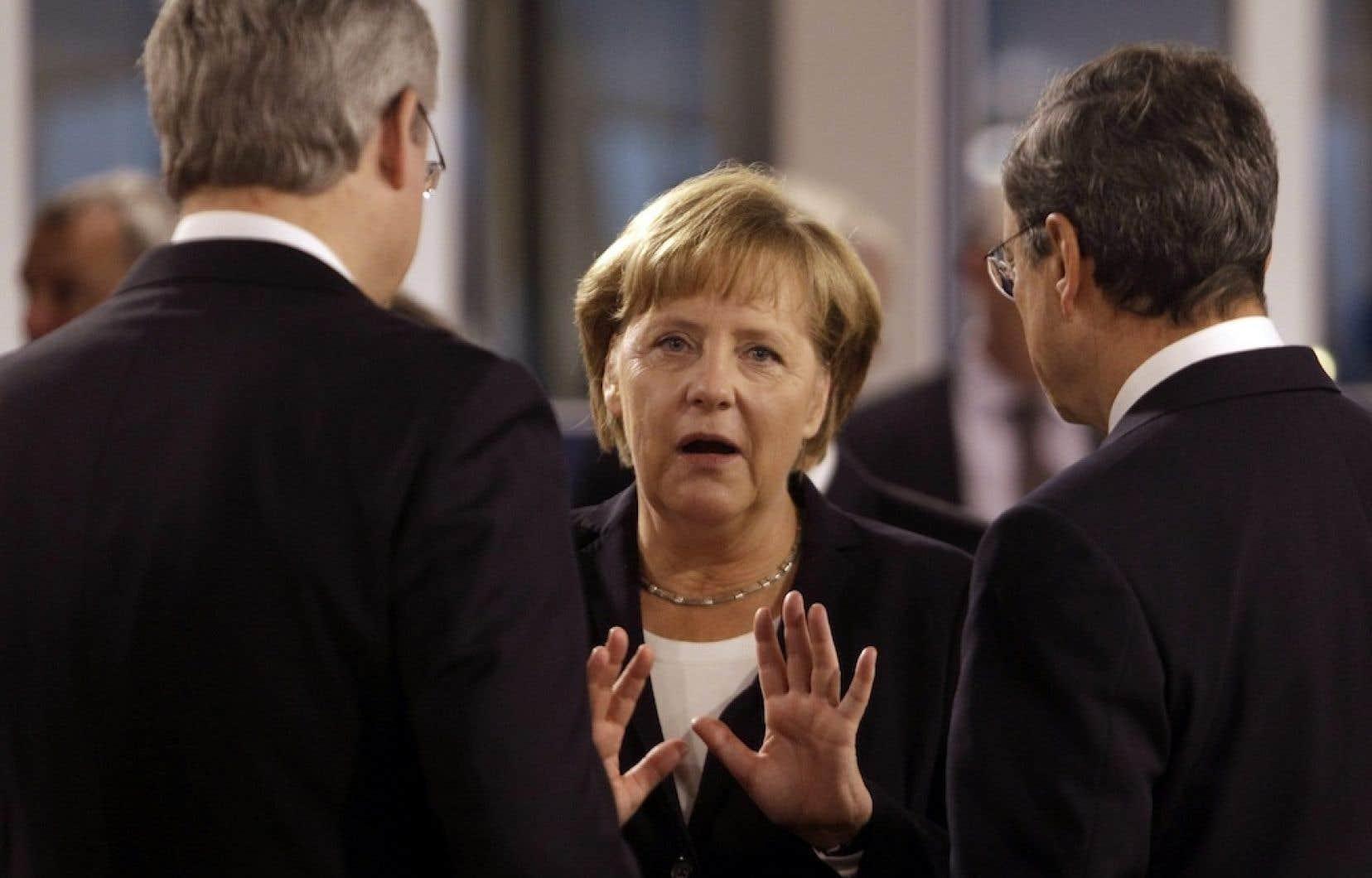La chancelière Angela Merkel avec Stephen Harper et le président de la Banque centrale européenne, Marco Draghi. Les négociations de libre-échange en cours entre le Canada et l'Europe présentent un côté politique beaucoup plus important qu'il n'y paraît.