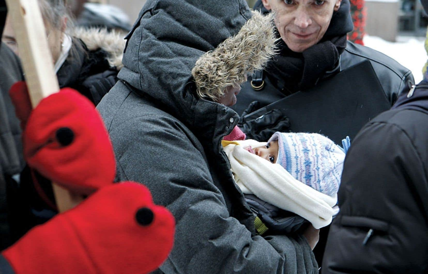 Une mère porte son enfant autiste lors d'une manifestation tenue en 2011 pour dénoncer l'absence de services offerts aux petits atteints de la maladie. Des parents manifesteront de nouveau aujourd'hui.