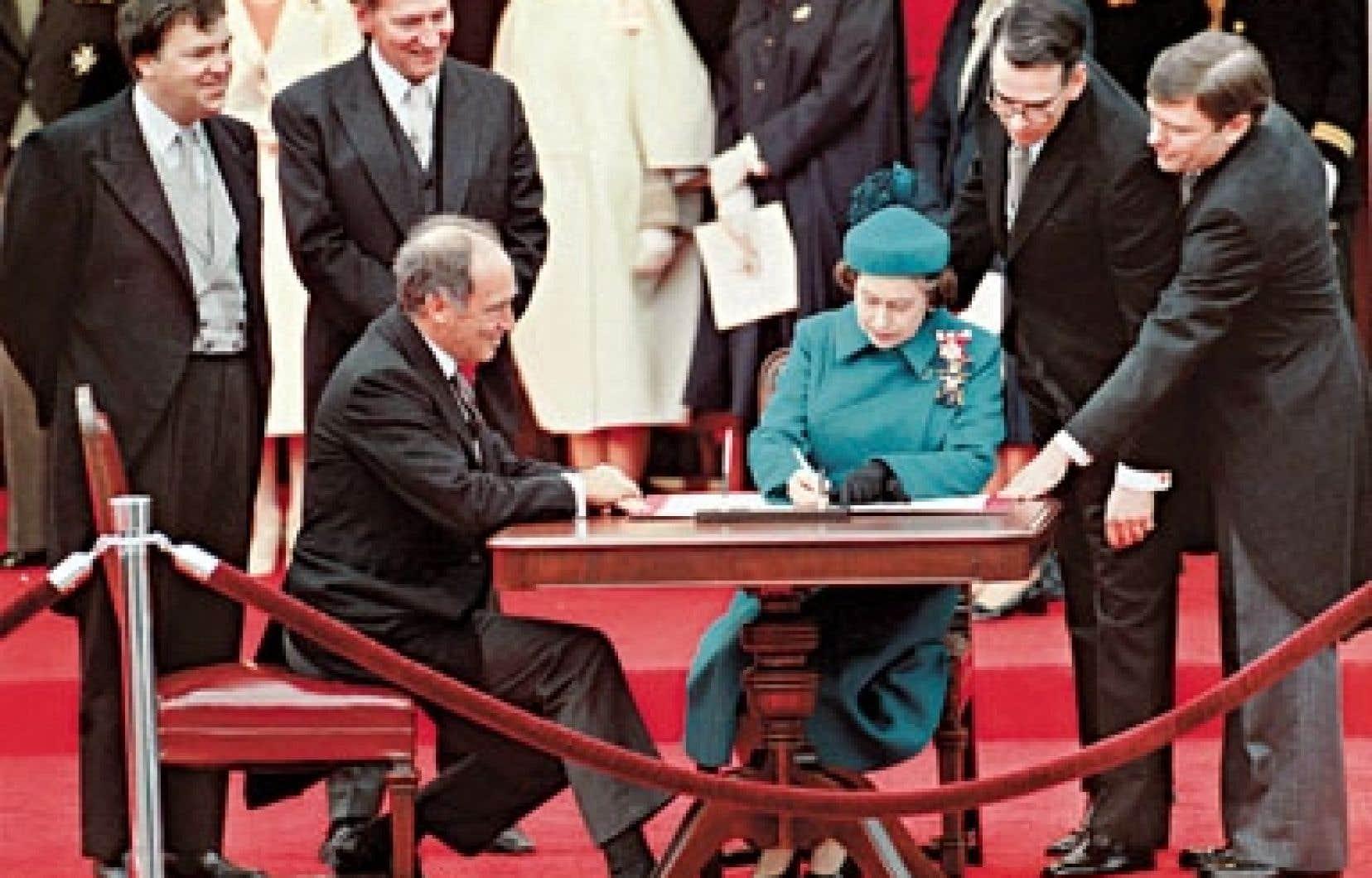 La reine Élisabeth II signant les documents de la Constitution, sous les regards du premier ministre Pierre Elliott Trudeau, le 17 avril 1982.