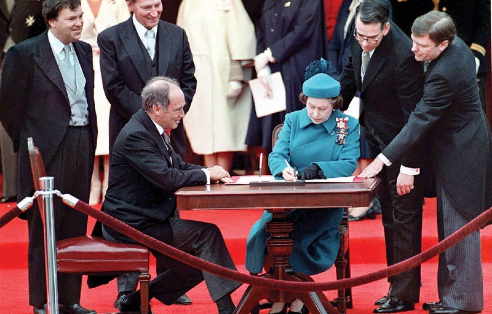 Pierre Elliott Trudeau et la reine Élisabeth II lors de la signature des documents constitutionnels.