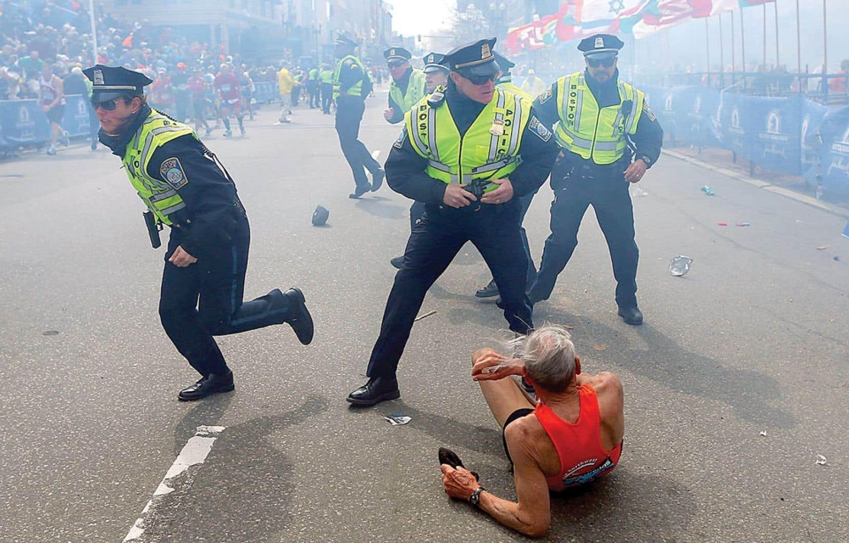 Un marathonien tombé par terre après l'explosion de la seconde bombe regarde des policiers courir autour de lui.