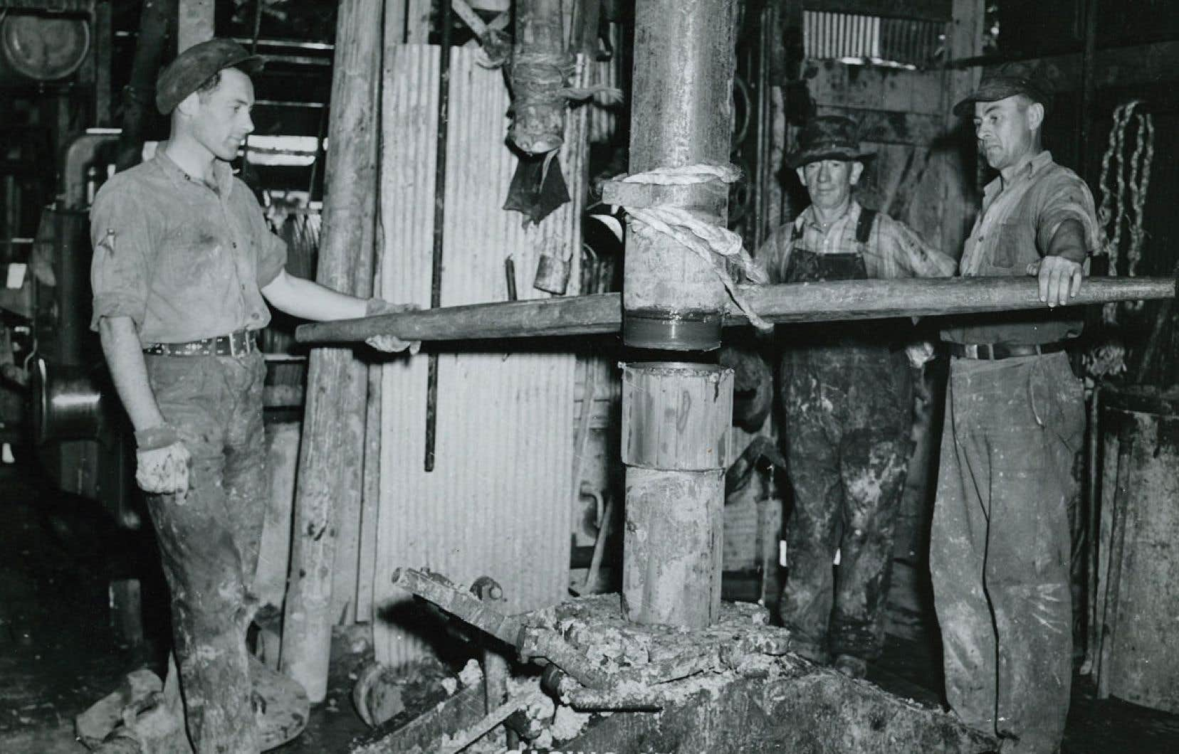 Des travailleurs s'affairent près de la mèche de forage d'un puits de la compagnie Gaspe Oil Ventures, à Rivière-Saint-Jean, près de Gaspé, en 1948. L'entreprise y a découvert des « indices » de pétrole.