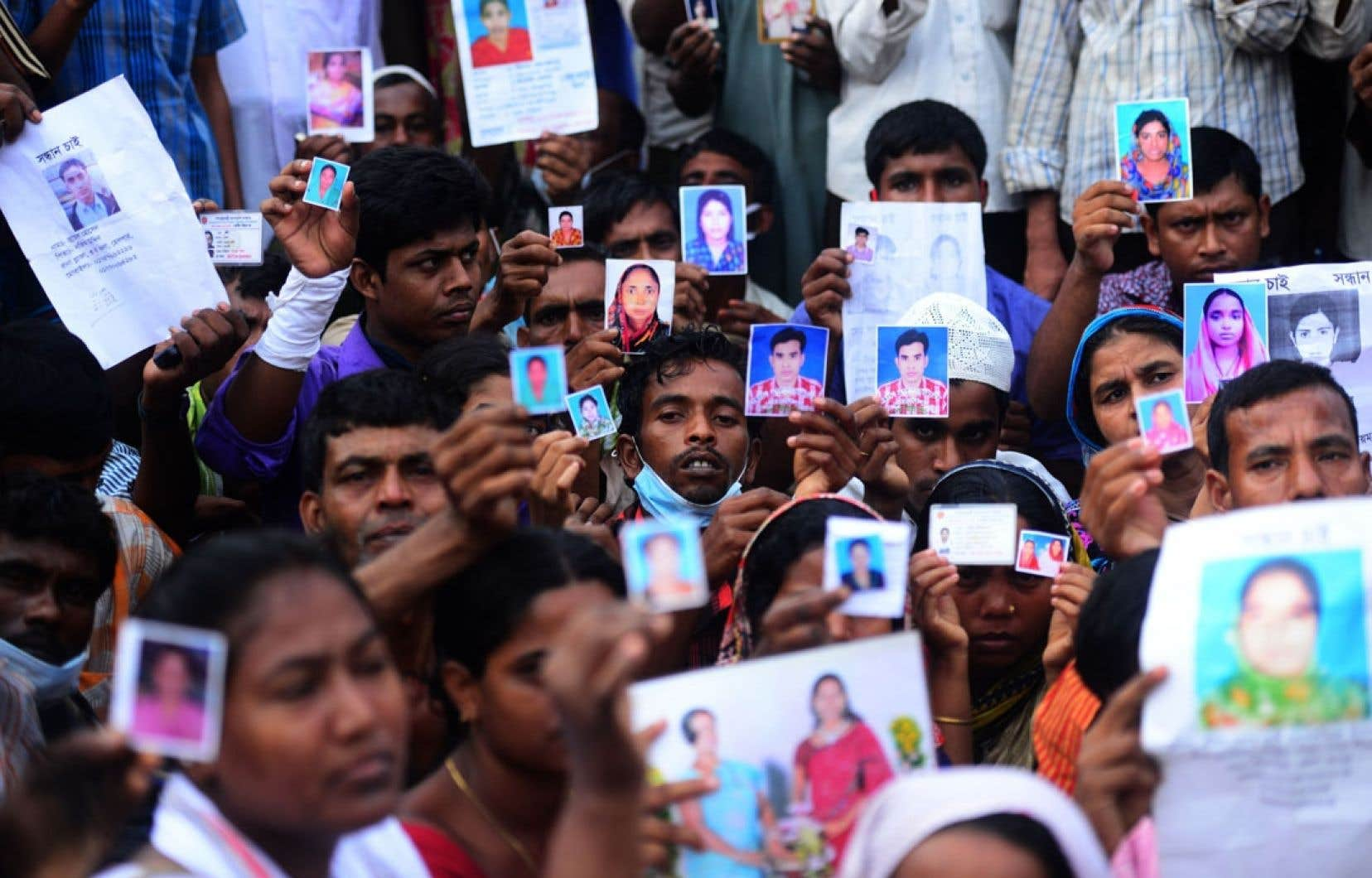Famille et compagnons de misère tiennent dans leurs mains les photos des travailleurs disparus dans l'effondrement d'un immeuble contenant des « ateliers de misère » dans la banlieue de Dacca.