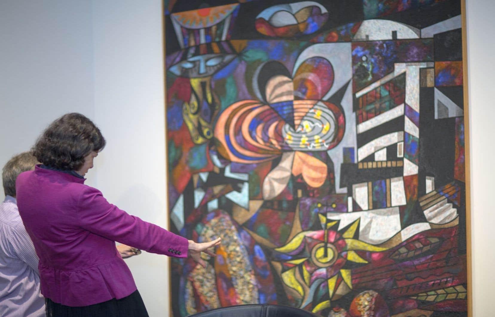 La directrice du MAC, Paulette Gagnon, montre une toile d'Alfred Pellan intitulée Calme obscur (1944-1947), peinte à l'huile de silice et comprenant du mâchefer.