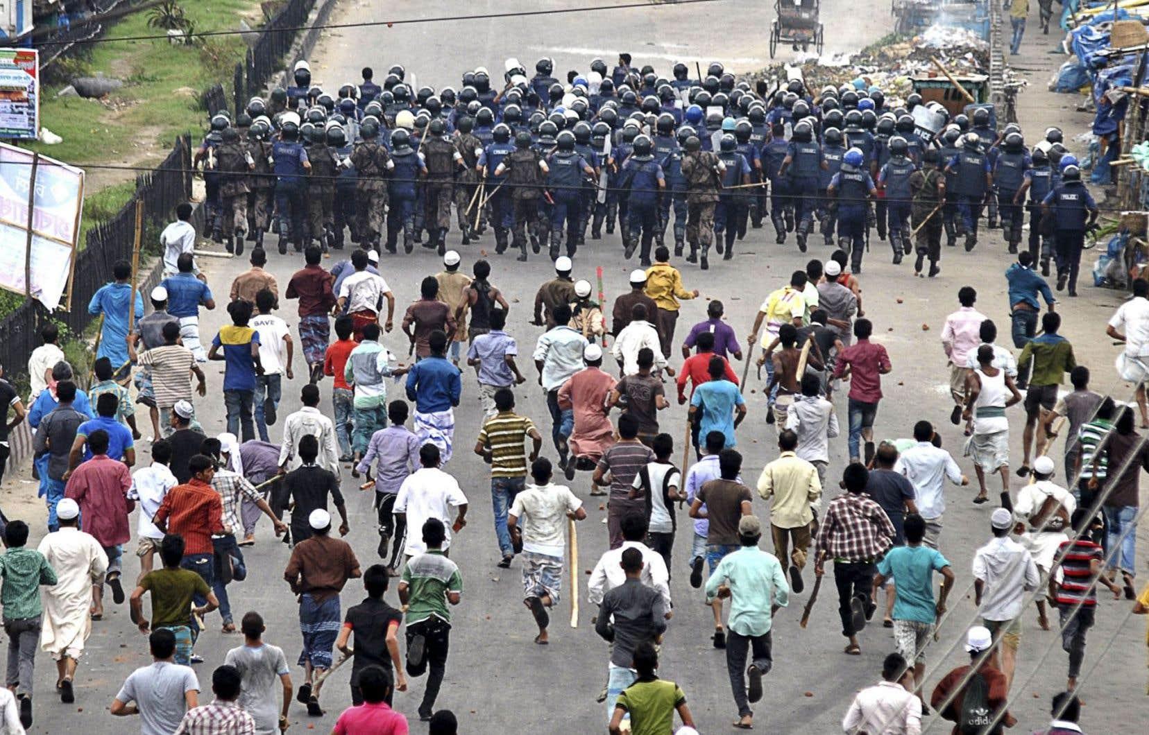 Des policiers fuient devant des manifestants.
