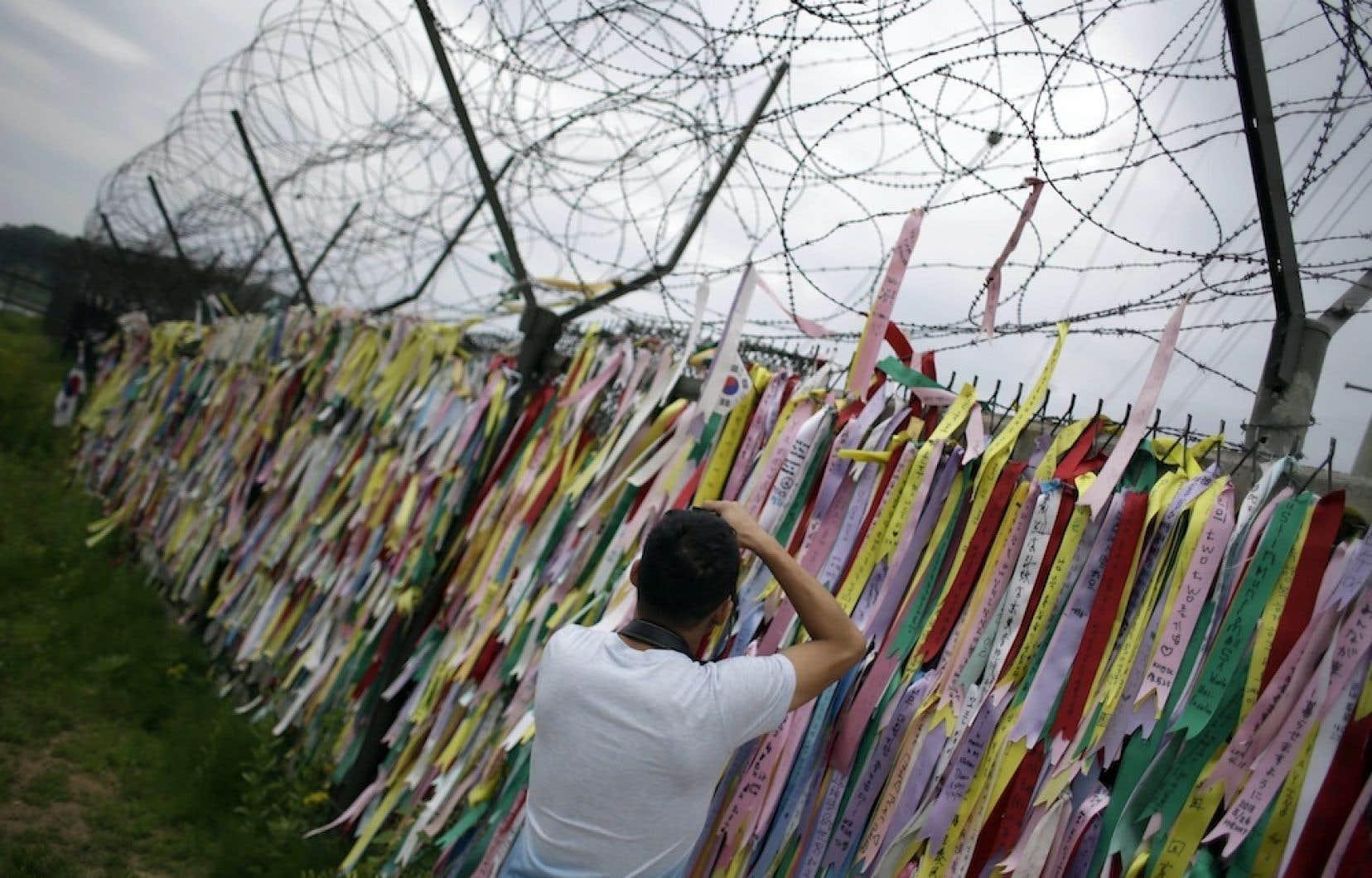 Un touriste prend des photos d'une clôture sur laquelle est accrochée plusieurs messages de réunification des Corées.