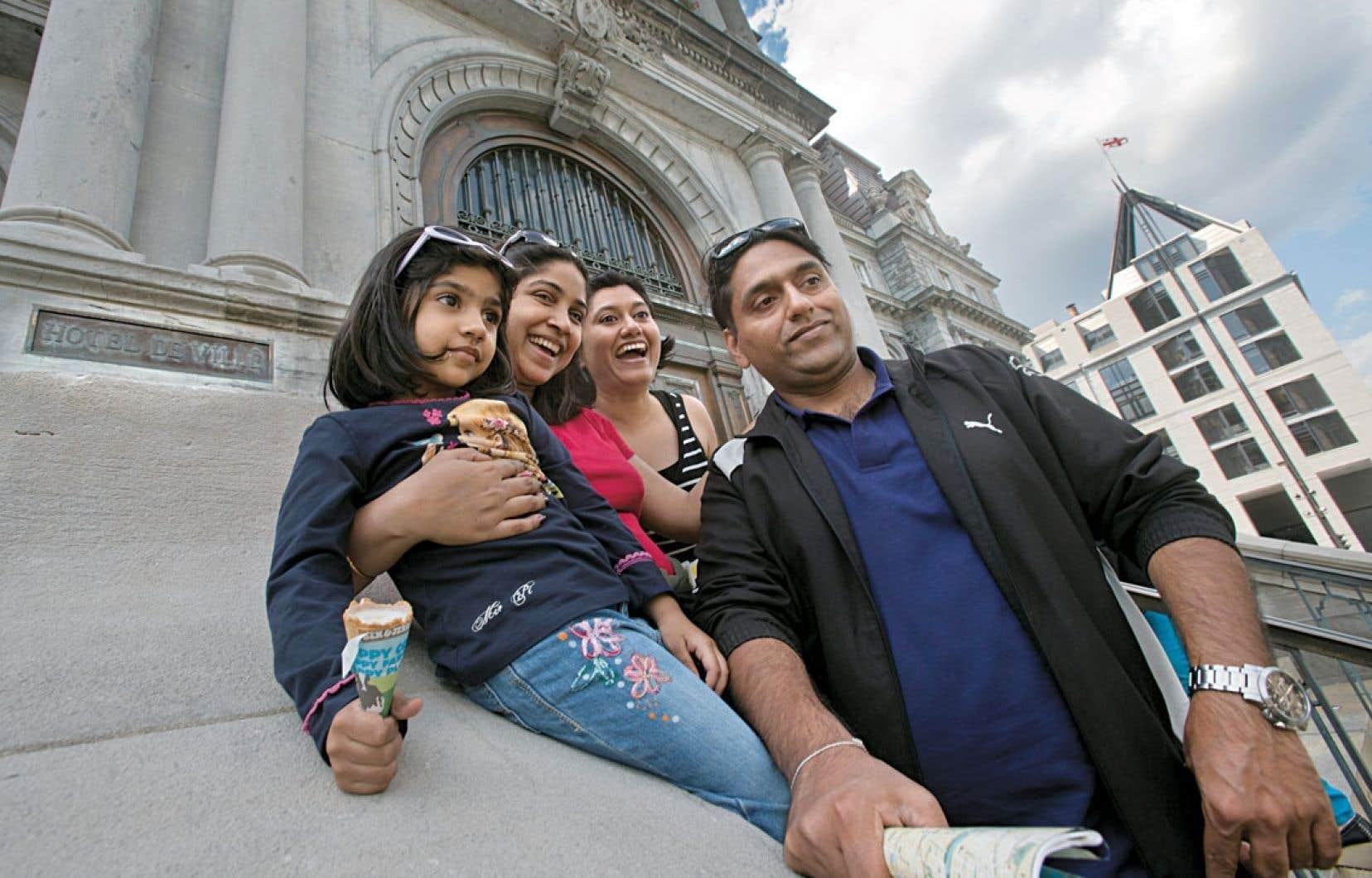 Des touristes indiens prennent la pose devant l'hôtel de ville de Montréal, crème glacée à la main.