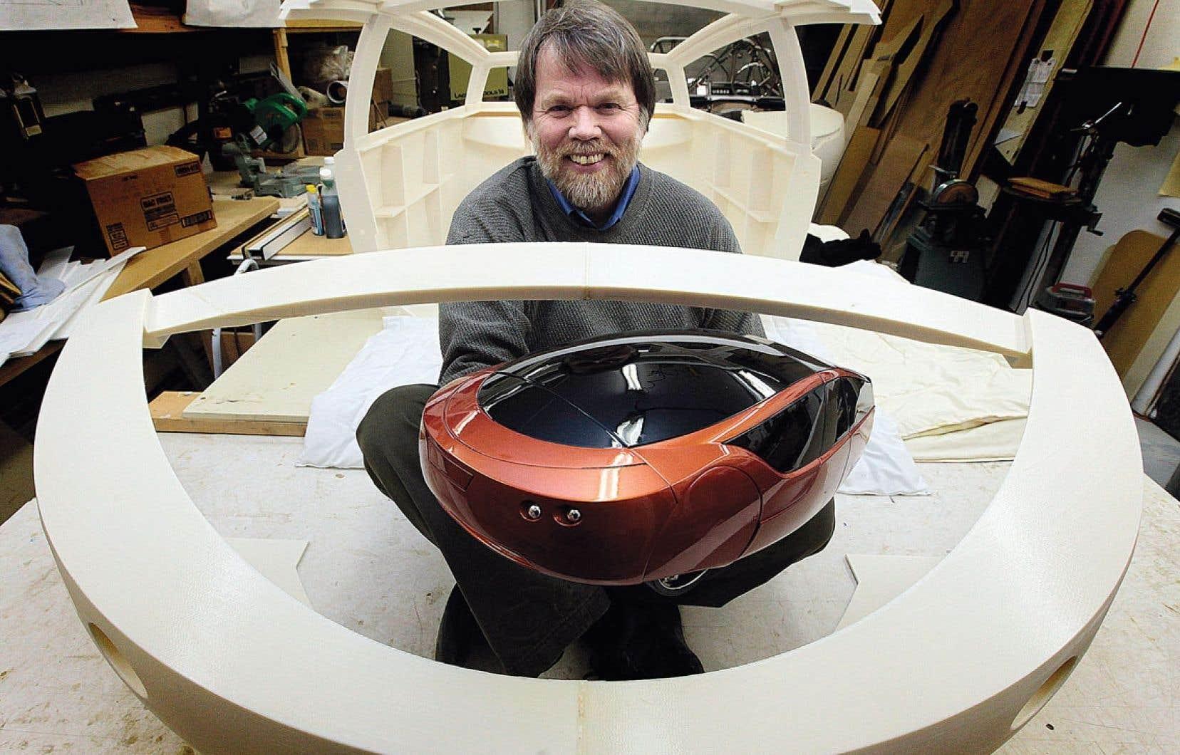 L'ingénieur Jim Kor, président de KOR EcoLogic, entouré de quelques panneaux de carrosserie de l'Urbee, qui ont été produits à l'aide d'une imprimante tridimensionnelle. Il tient une maquette à 1/6 de l'Urbee, elle aussi produite à l'aide d'une imprimante 3D.