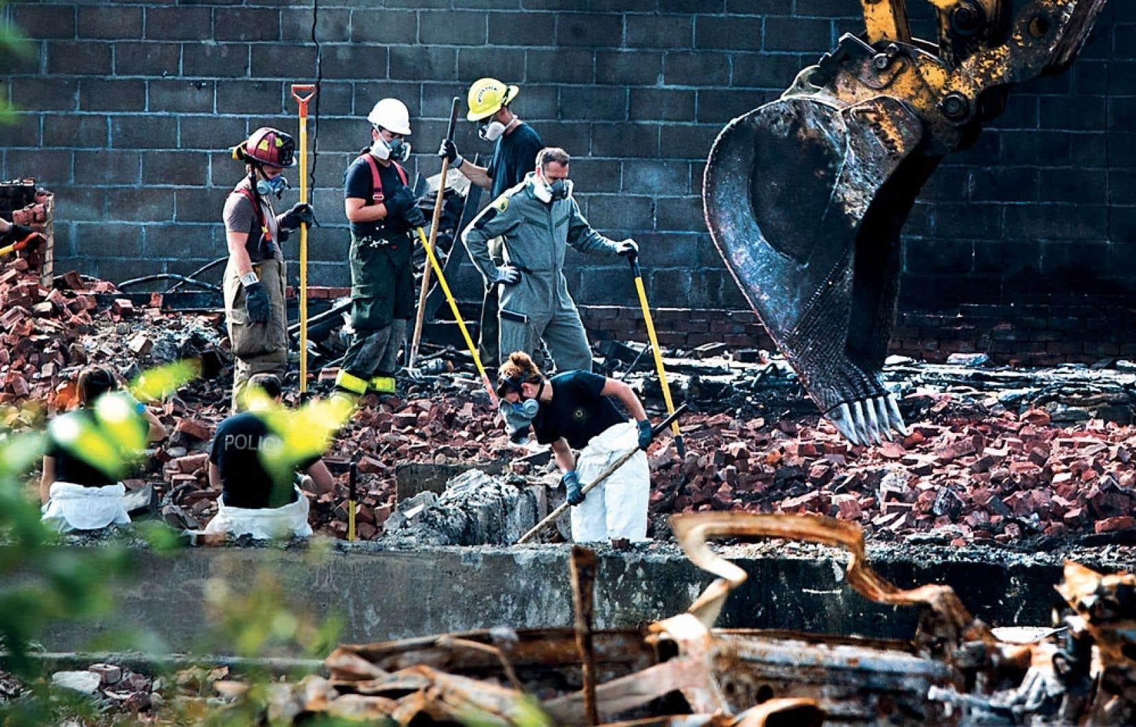 Des enquêteurs de la Sûreté du Québec fouillant les décombres au cœur de la «zone rouge», à Lac-Mégantic, dimanche.
