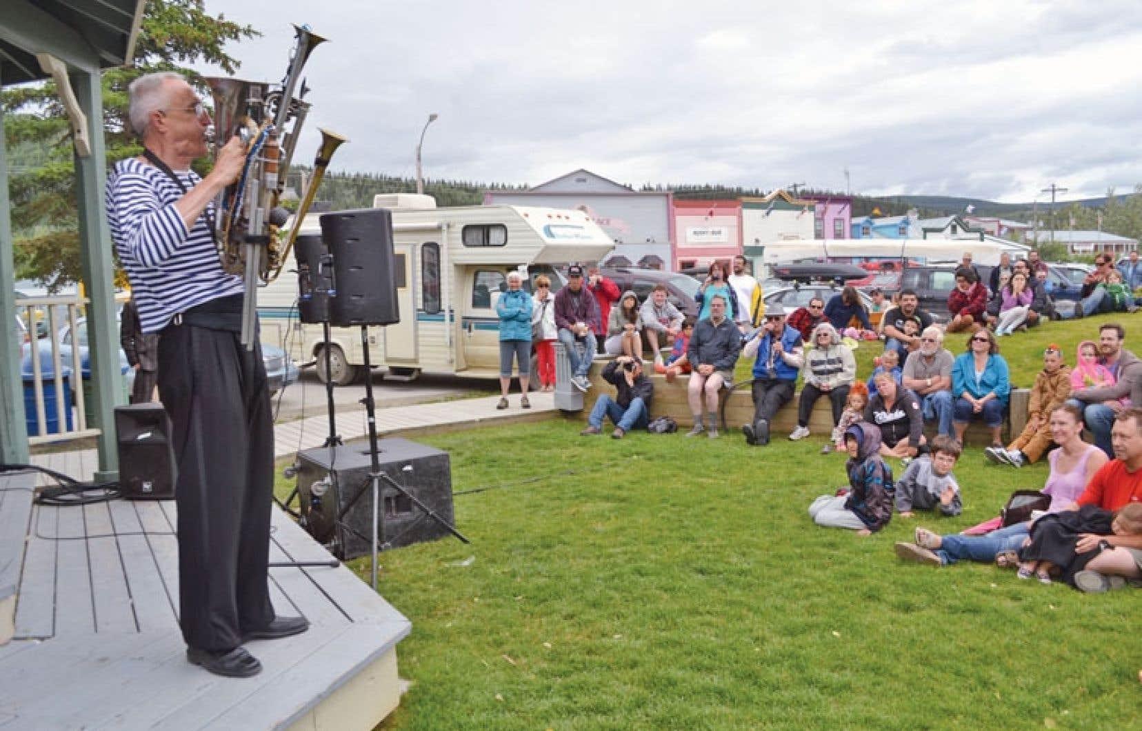 Des festivaliers installés à la bonne franquette devant une scène extérieure, dimanche, à Dawson City