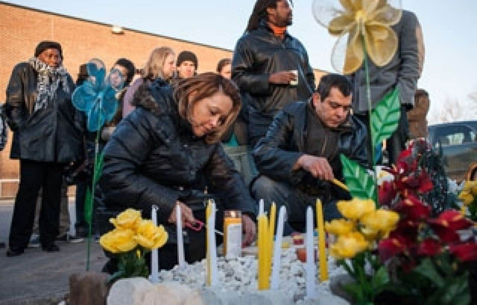 Les parents de Freddy Villanueva, Gilberto Villanueva et Lilian Madrid Antunes, allument une bougie au pied du mémorial, le 6 avril 2013, pour célébrer l'anniversaire de naissance de leur fils. Il aurait eu 23 ans.