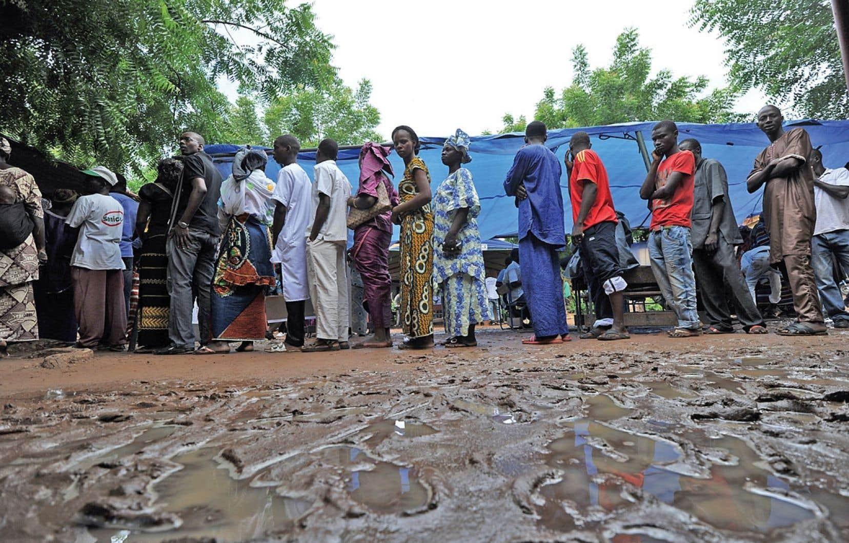 Des Maliens attendaient en file les deux pieds dans la boue devant un bureau de vote de Bamako, dimanche.