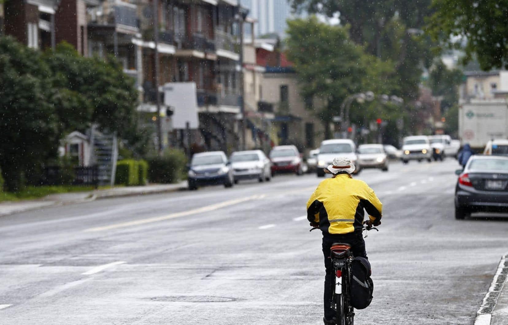 Si les canards ne sillonnent plus le secteur, le temps de canard, lui, n'a pas fait ses adieux. Ce cycliste roule sous la pluie.