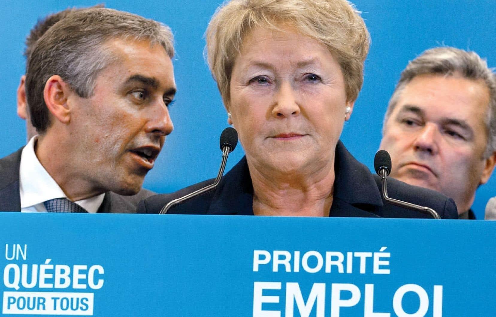 La première ministre Pauline Marois entourée du ministre des Finances et de l'Économie, Nicolas Marceau, et du député Daniel Breton, lundi à Montréal.