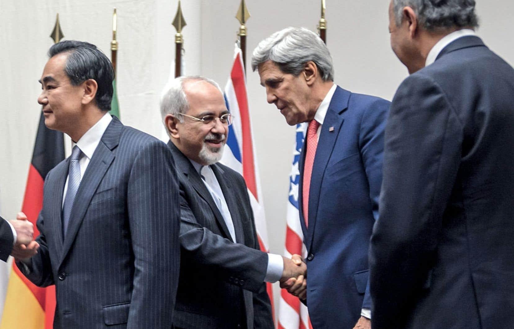 Le secrétaire d'État américain, John Kerry, serre la main du ministre iranien des Affaires étrangères, Mohammad Javad Zarif, en présence des ministres chinois et français des Affaires étrangères, Wang Yi et Laurent Fabius, dimanche à Genève, après la conclusion d'un accord intermédiaire sur la question nucléaire iranienne.