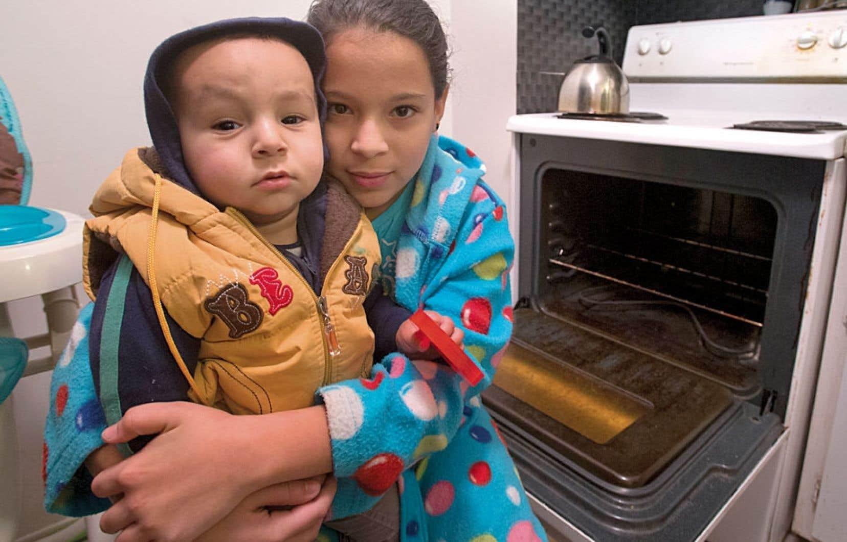 Les enfants de Jaouad Alaoui se réchauffent près du four de l'appartement familial, où le chauffage et l'eau chaude sont en panne depuis des jours. Des centaines d'autres locataires de deux immeubles vivent le même cauchemar dans l'arrondissement Saint-Laurent, à Montréal.