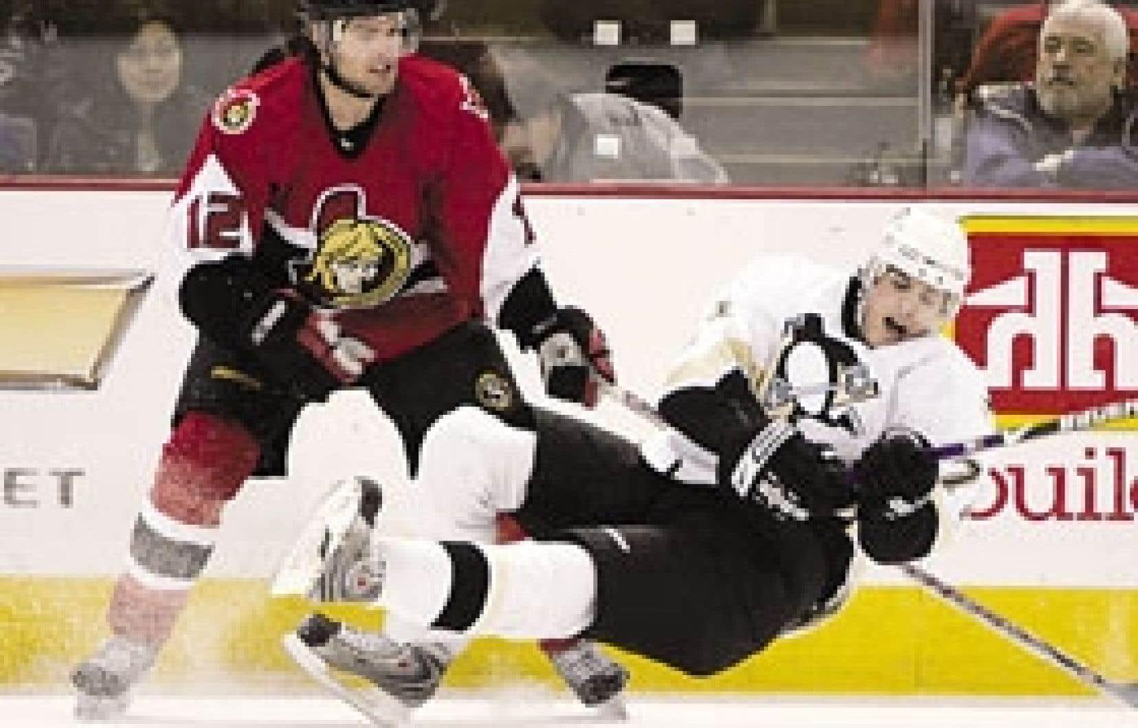 Mike Fisher, des Sénateurs, a servi une dure mise en échec à Evgeny Malkin, des Penguins de Pittsburgh, en deuxième période lors du premier match à Ottawa, mercredi. Les joueurs des Penguins comptent remettre la monnaie de leur pièce à leurs adve