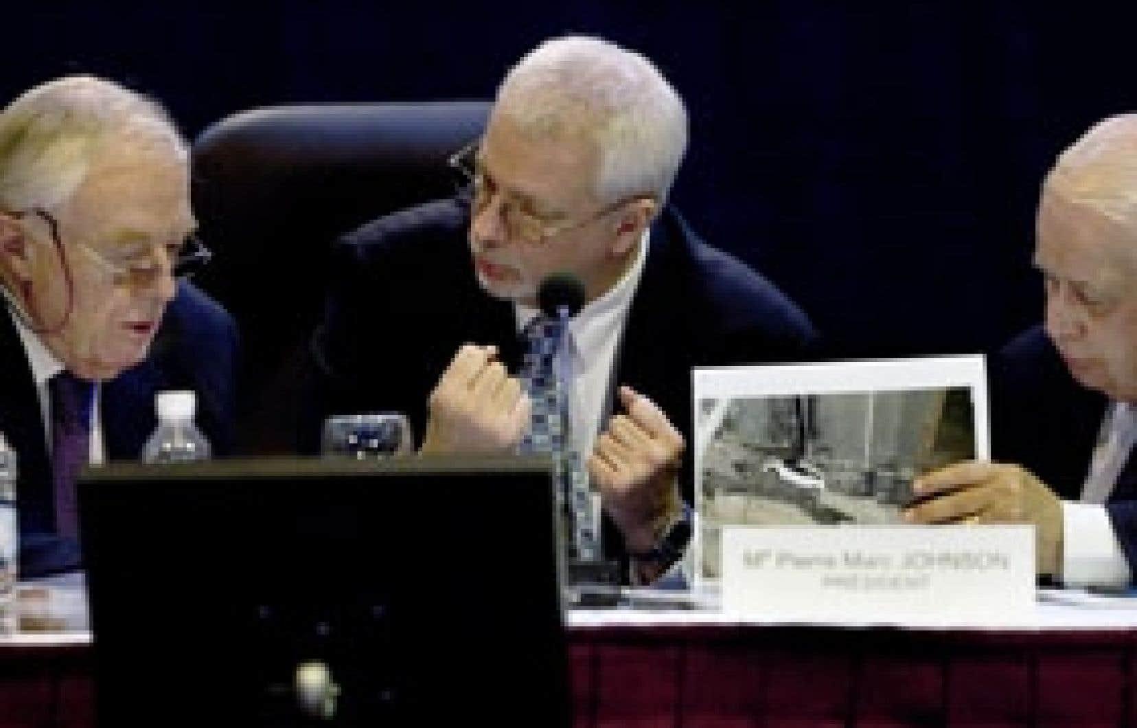 Le président de la Commission sur l'effondrement du viaduc de la Concorde, Pierre Marc Johnson, et les commissaires Armand Couture et Roger Nicolet examinent des photos du viaduc détruit.