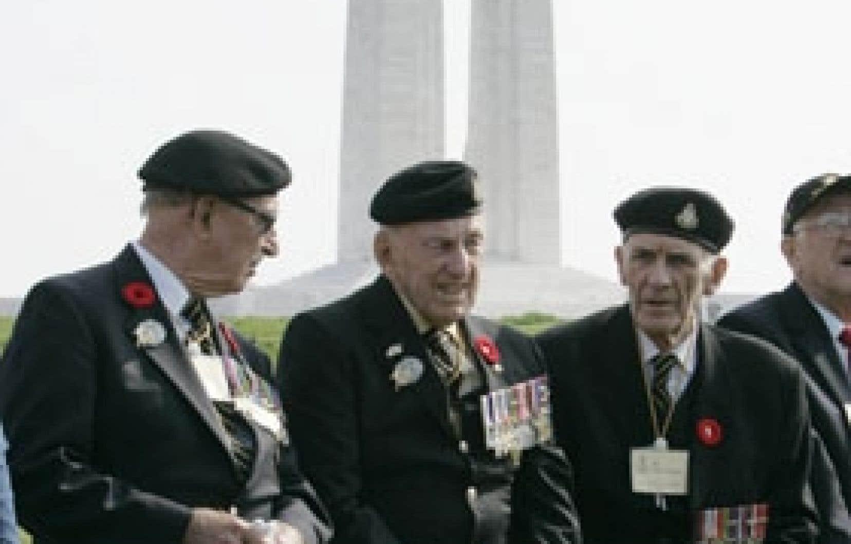 Des vétérans canadiens discutent en attendant le début des cérémonies commémorant le 90e anniversaire de la bataille de Vimy. En arrière-plan, le mémorial canadien aux soldats décédés lors de la Première Guerre mondiale.
