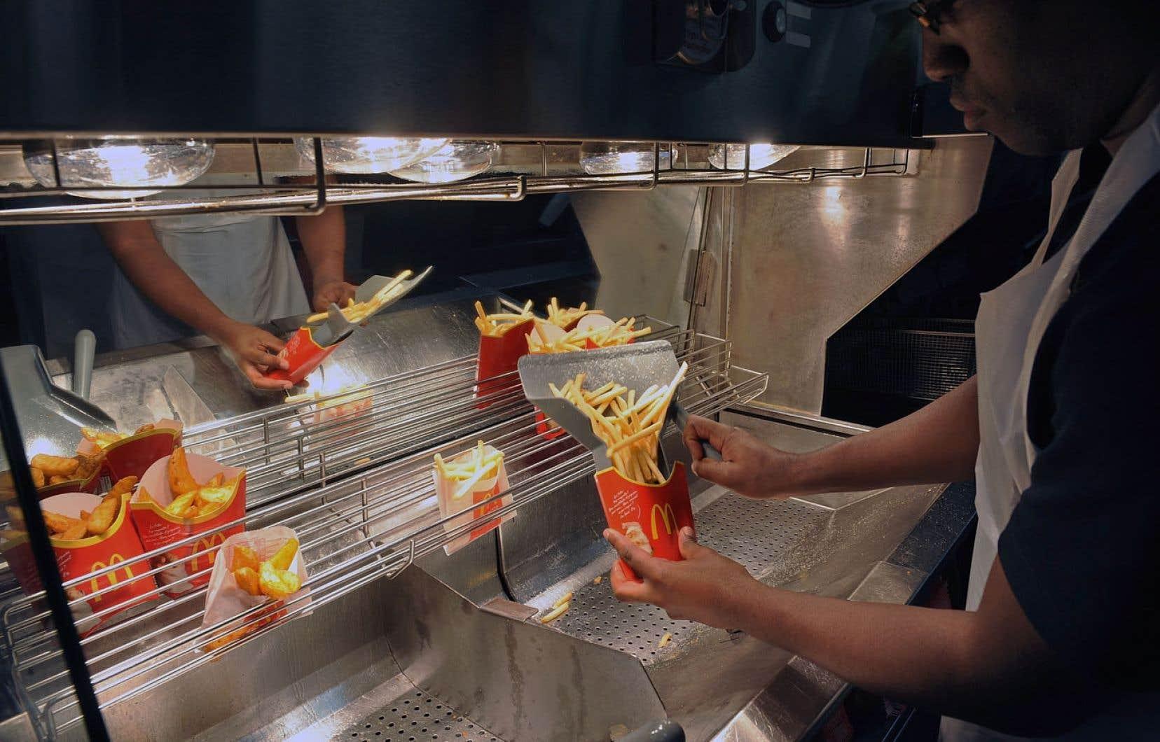 Dans un restaurant McDonald's à Ramonville-Saint-Agne, en France, un employé sert des frites. L'entreprise n'aurait pas contribué au fisc français sa juste part d'impôts.
