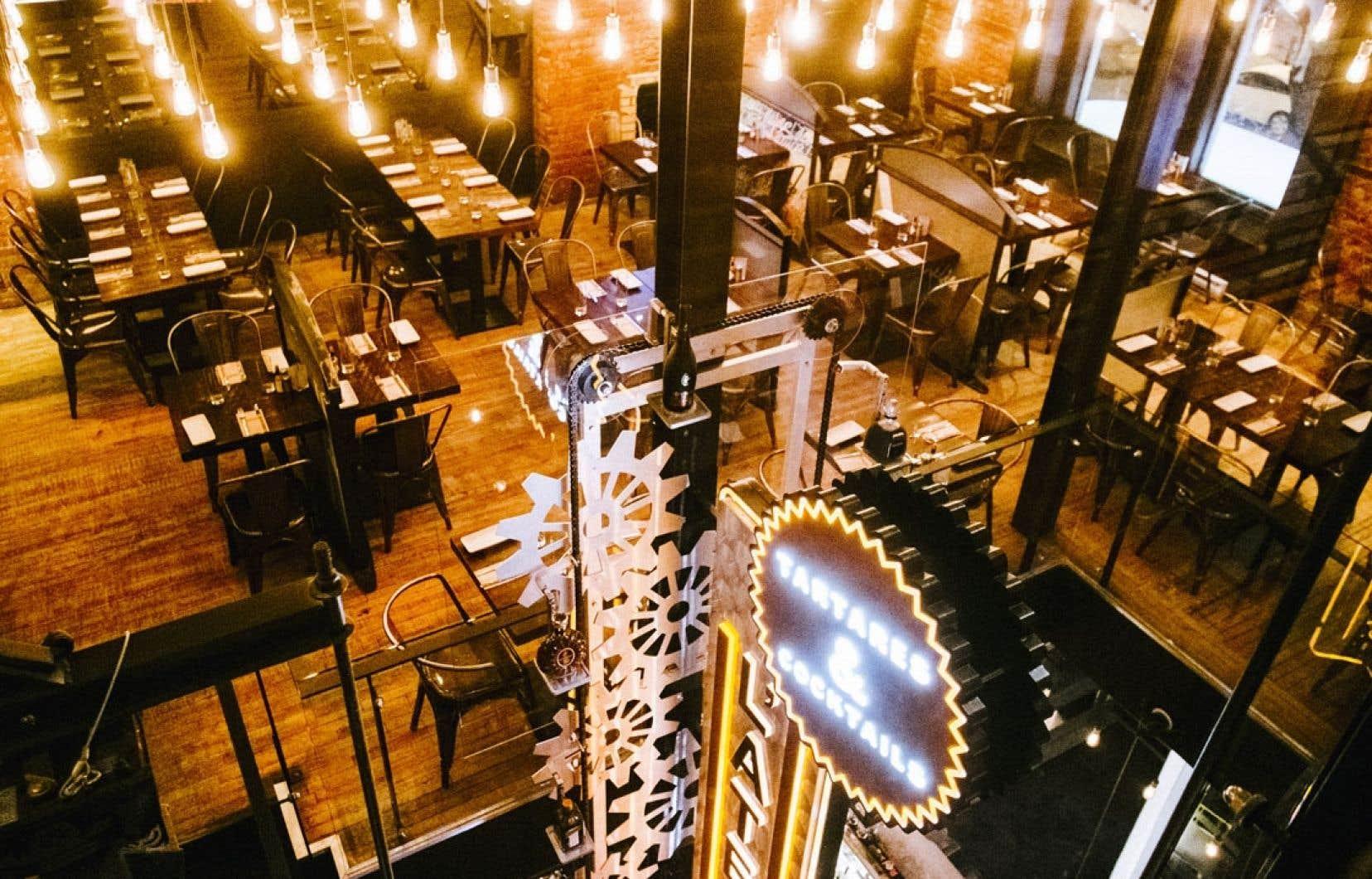 Le décor du restaurant évoque un atelier de travail, avec engrenages surdimensionnés et ampoules électriques.