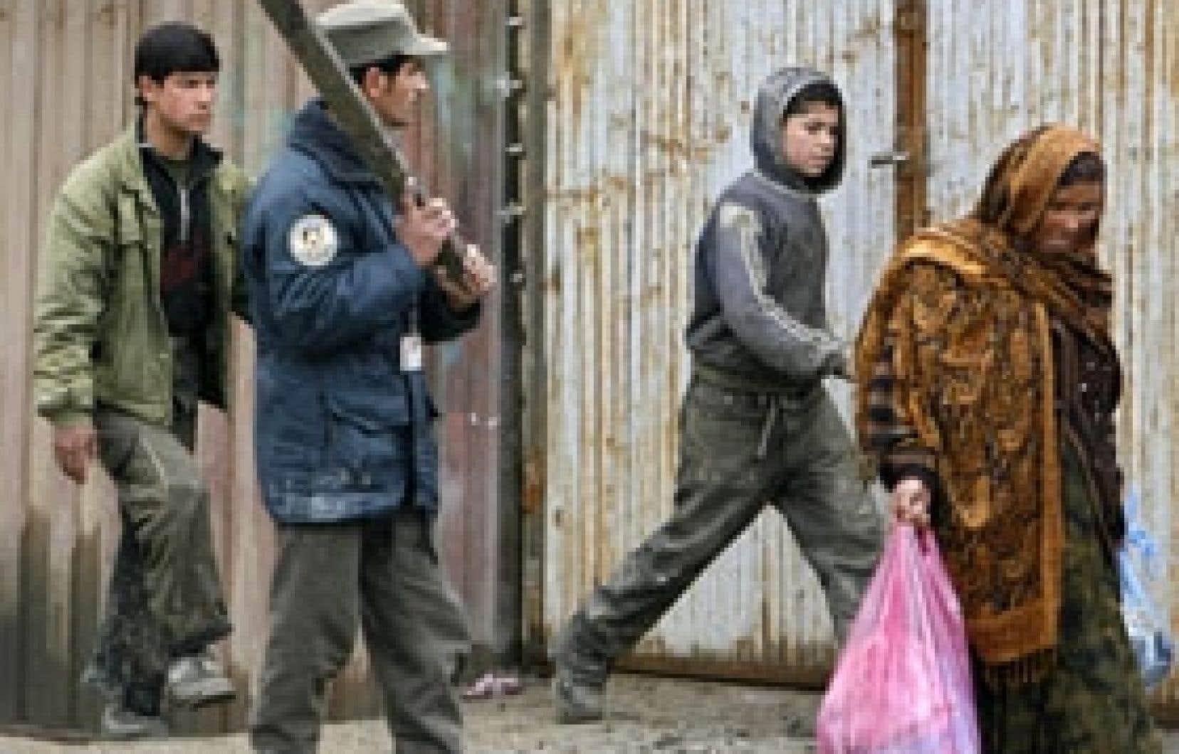 Un policier afghan empêchait hier des piétons de s'approcher du site d'un attentat.