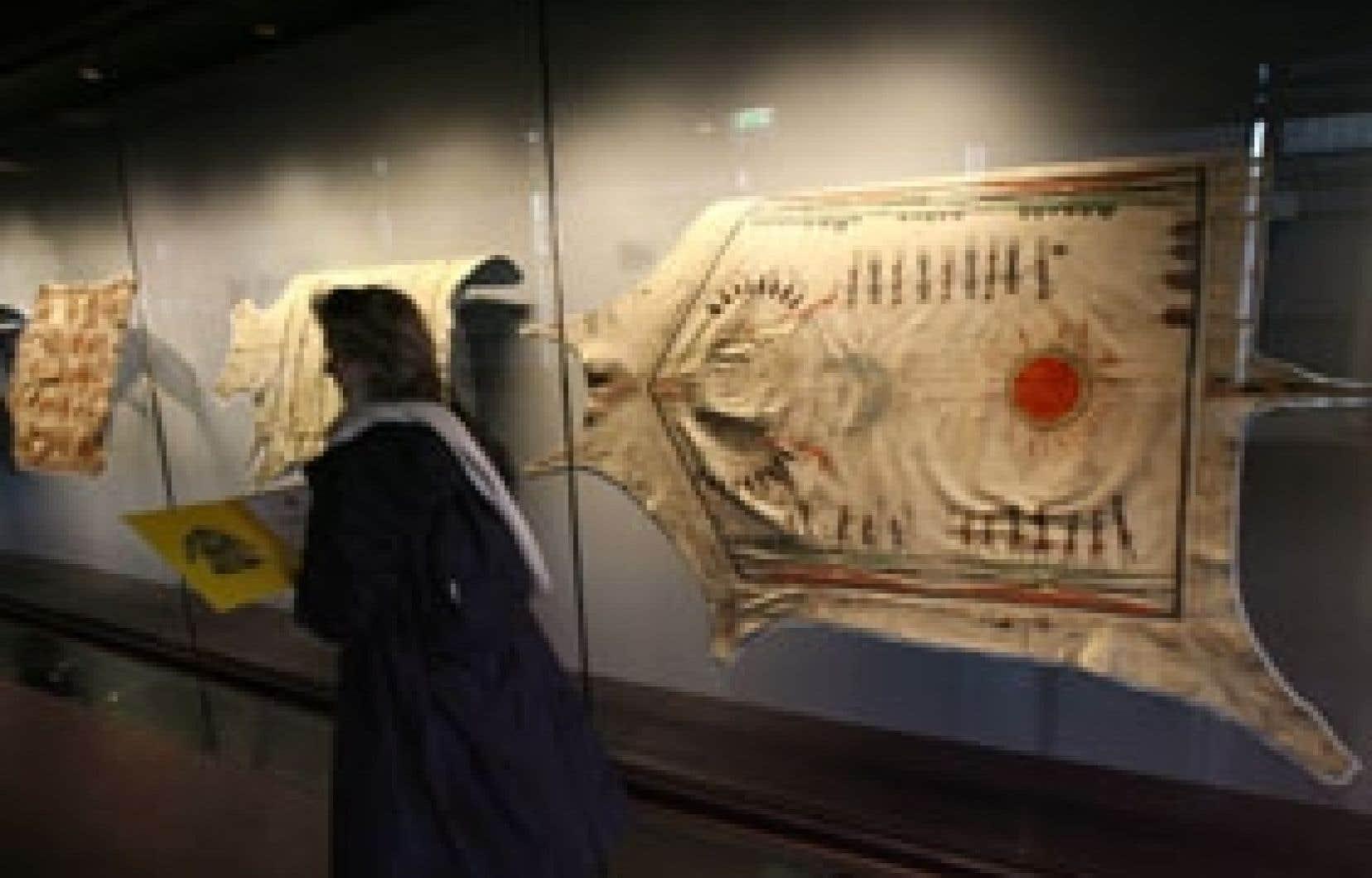 Une visiteuse parcourt une section du Musée du Quai Branly où sont exposées des peaux peintes par des Amérindiens à l'époque des premiers voyages des Français en Amérique. Le musée parisien consacre une exposition aux Collections royales fran