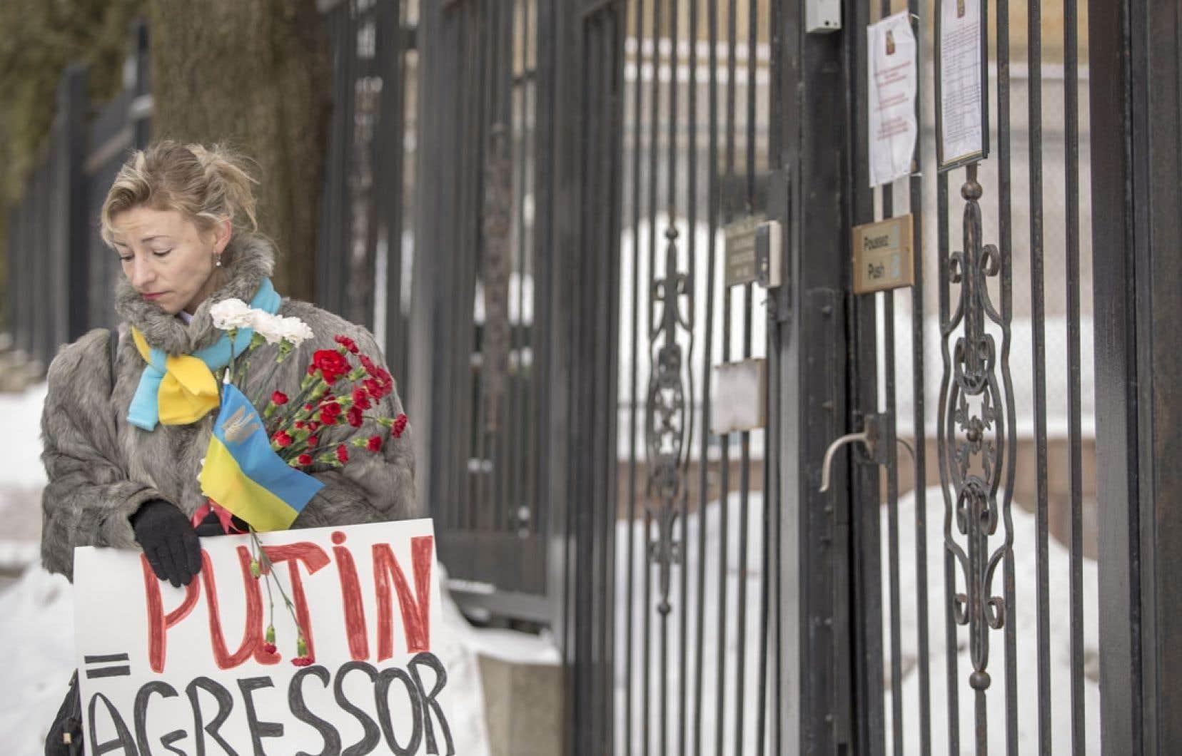Une manifestante portant les couleurs de l'Ukraine se tenait dimanche devant le consulat général de Russie, à Montréal.
