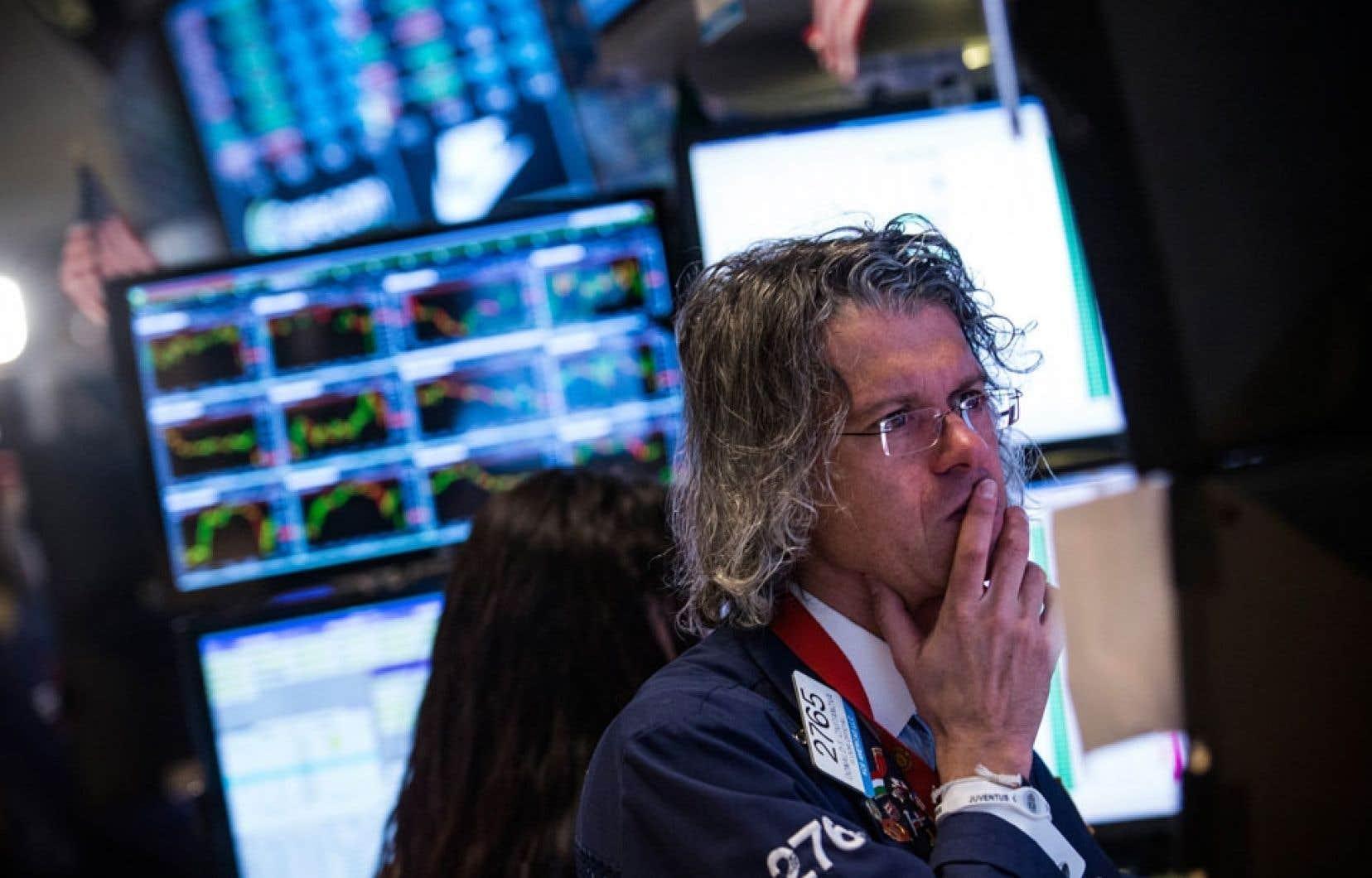 Un courtier de la Bourse de New York observe les données qui défilent sur les écrans.