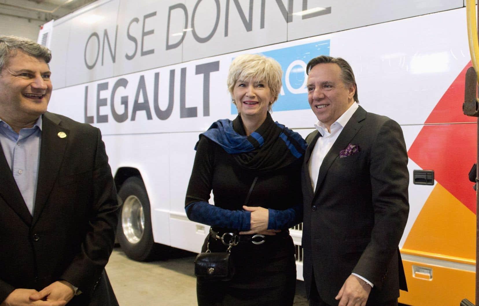 Entouré de sa femme, Isabelle Blais, et du député Gérard Deltell, François Legault a dévoilé mardi son autobus de campagne tapissé du slogan de la CAQ «On se donne Legault».