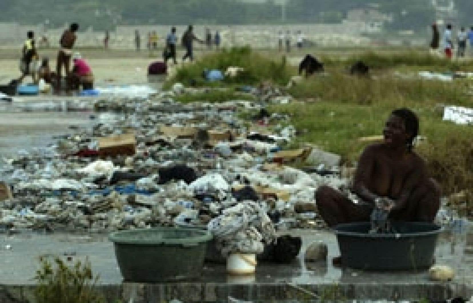 Des femmes lavent du linge à un point d'eau dans un parc du centre-ville de Port-au-Prince, la capitale haïtienne. Les problèmes d'évacuation d'eaux usées et d'adduction d'eau dans les villes et les villages sont parmi les plus importants