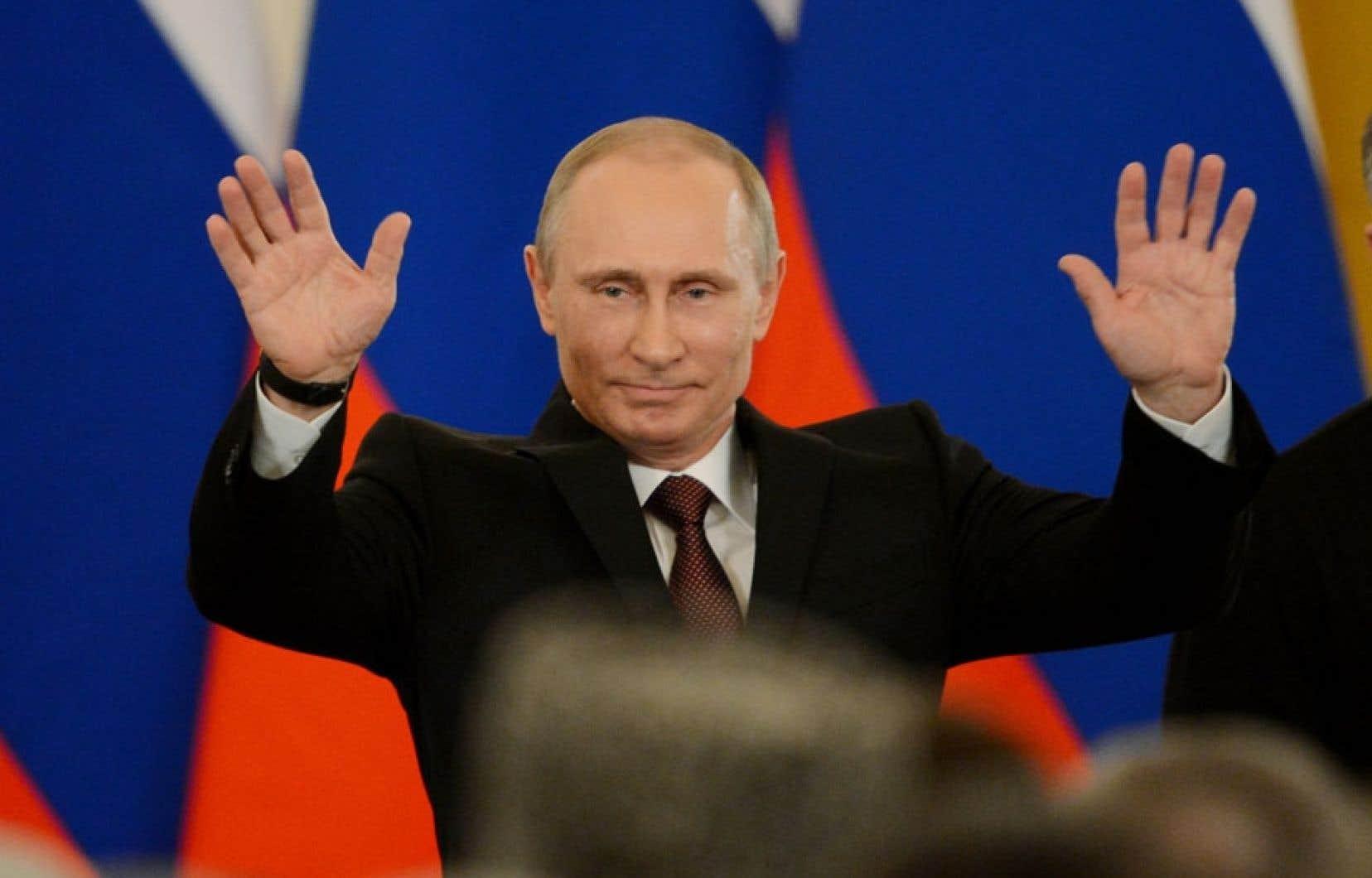 Le président russe, Vladimir Poutine, levant les bras après avoir a signé un traité qui rattache officiellement la Crimée à la Russie, mardi à Moscou.