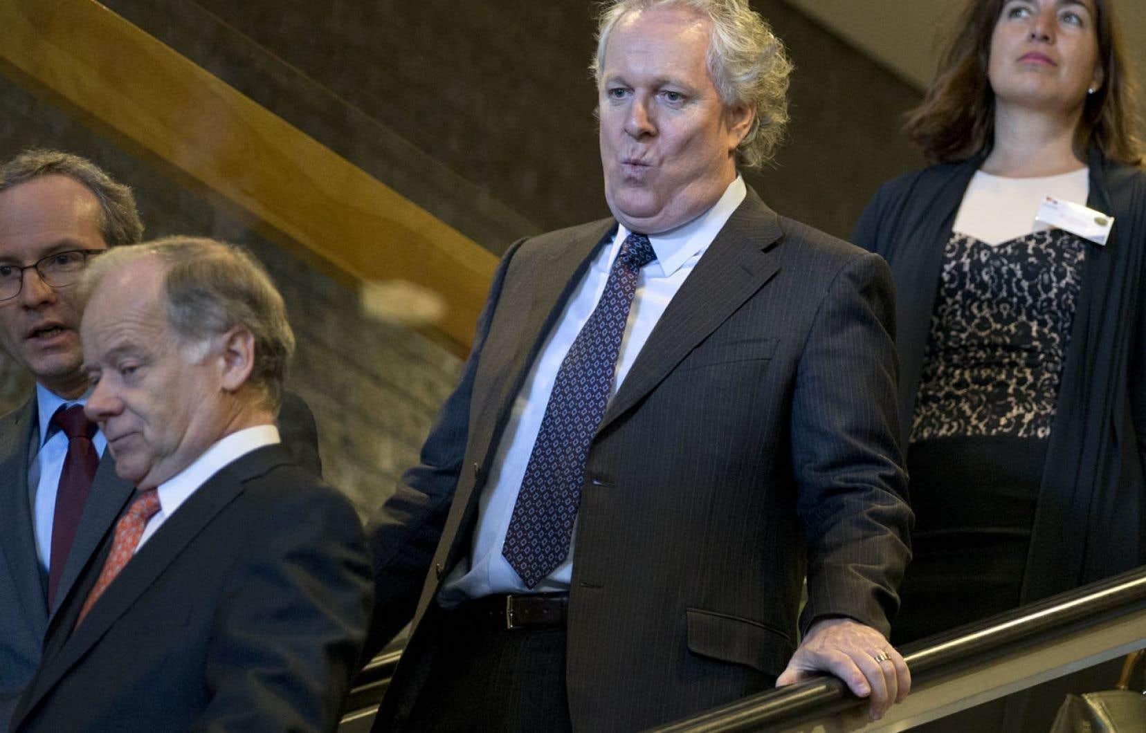 L'ancien premier ministre Jean Charest, accompagné de l'ex-ministre Raymond Bachand (à gauche), était invité lundi à prononcer une allocution devant la Chambre de commerce française au Canada. Son héritage politique refait surface dans la campagne électorale.