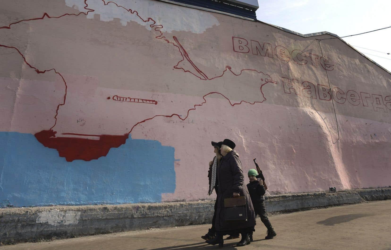 À Moscou, deux femmes et un enfant — kalachnikov jouet à la main — passent devant une murale inachevée montrant la péninsule de Crimée avec un slogan: «Uni pour toujours».