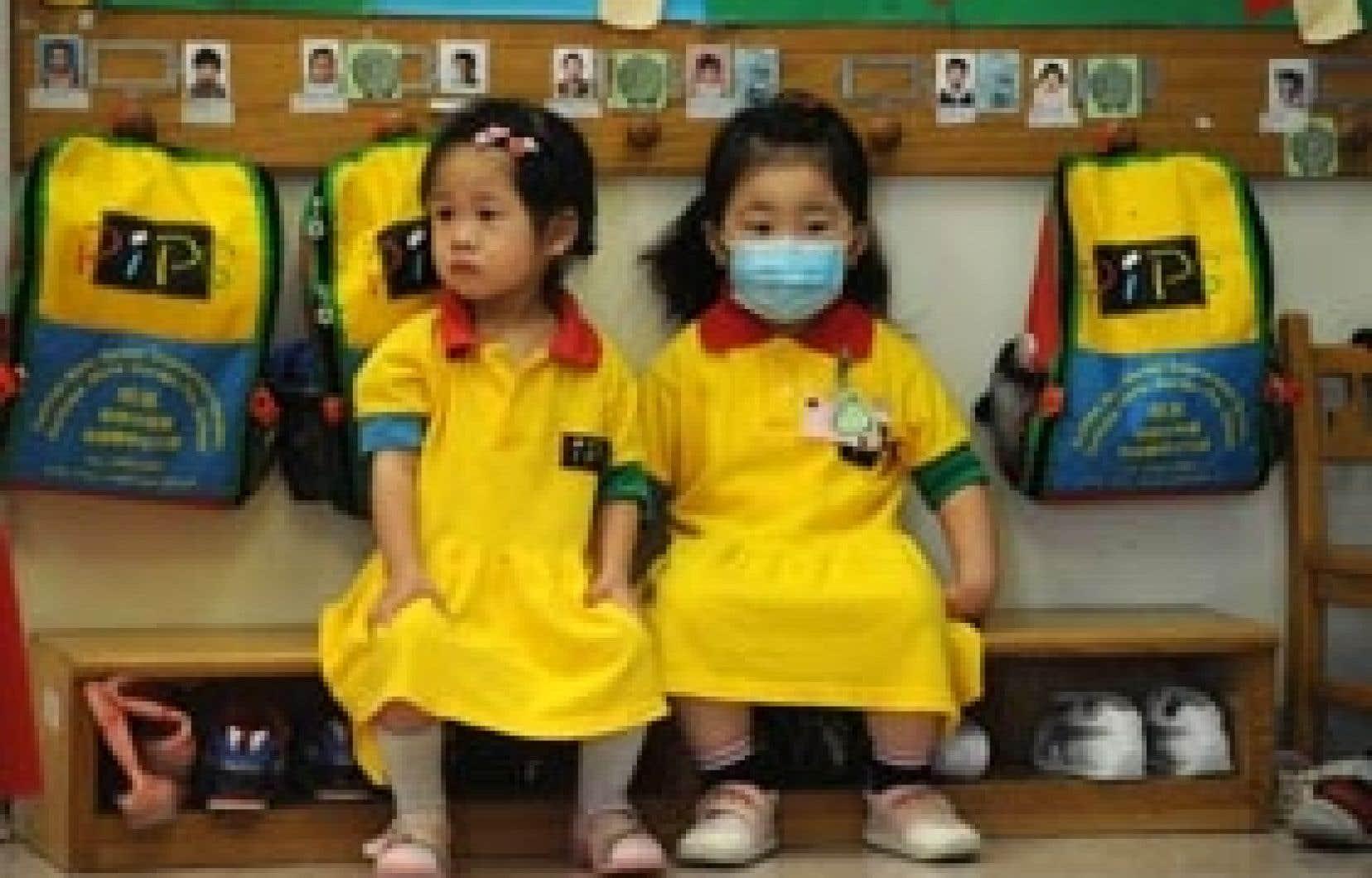 mike clarke afp Deux petites Chinoises, l'une portant un masque, l'autre pas, dans une garderie de Hong Kong. Les autorités ont fermé hier et pour une période de deux semaines toutes les écoles primaires pour éviter la propagation du virus de l