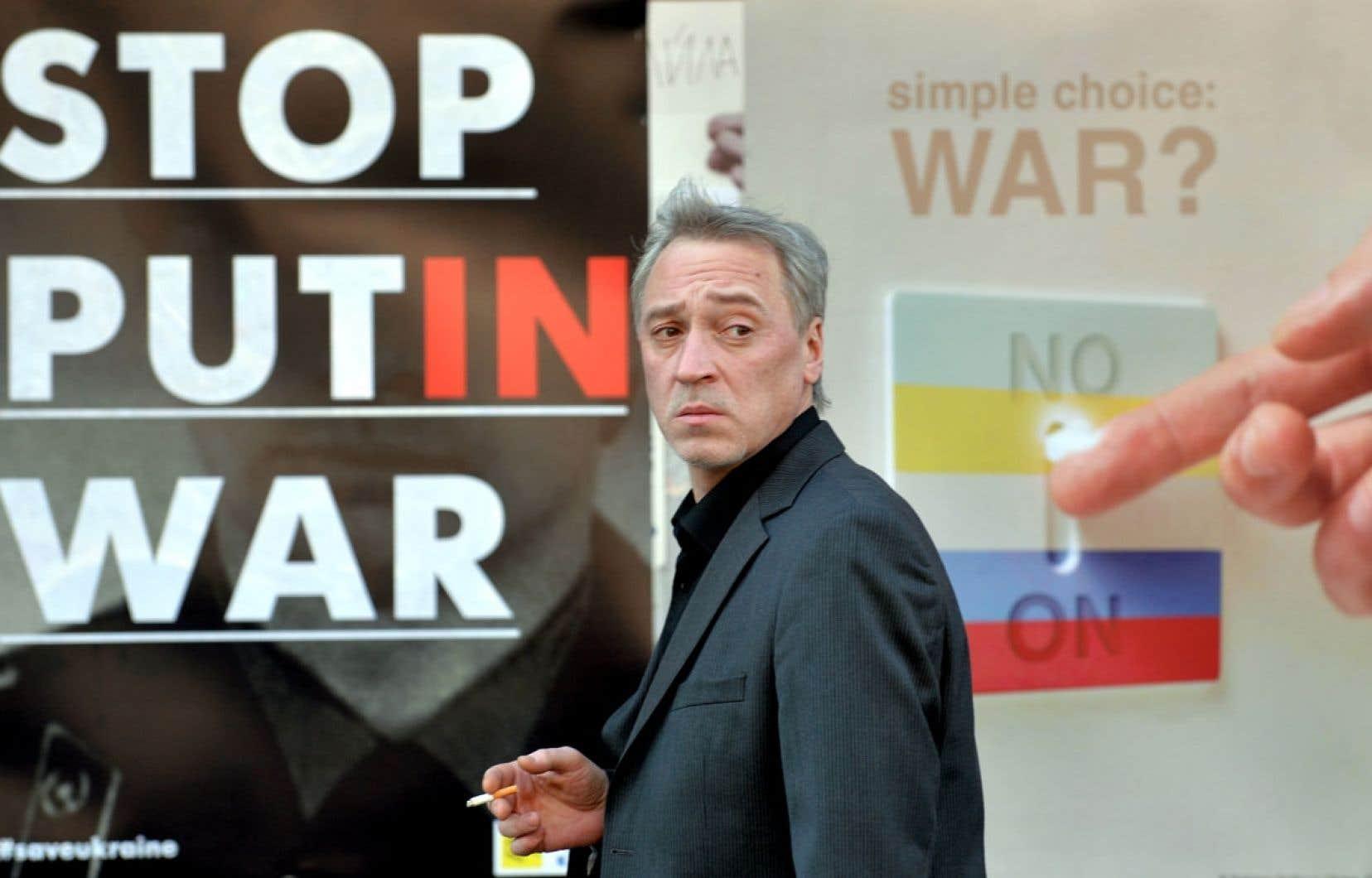 À Kiev, un homme passe devant une affiche invitant à arrêter la guerre de Vladimir Poutine.
